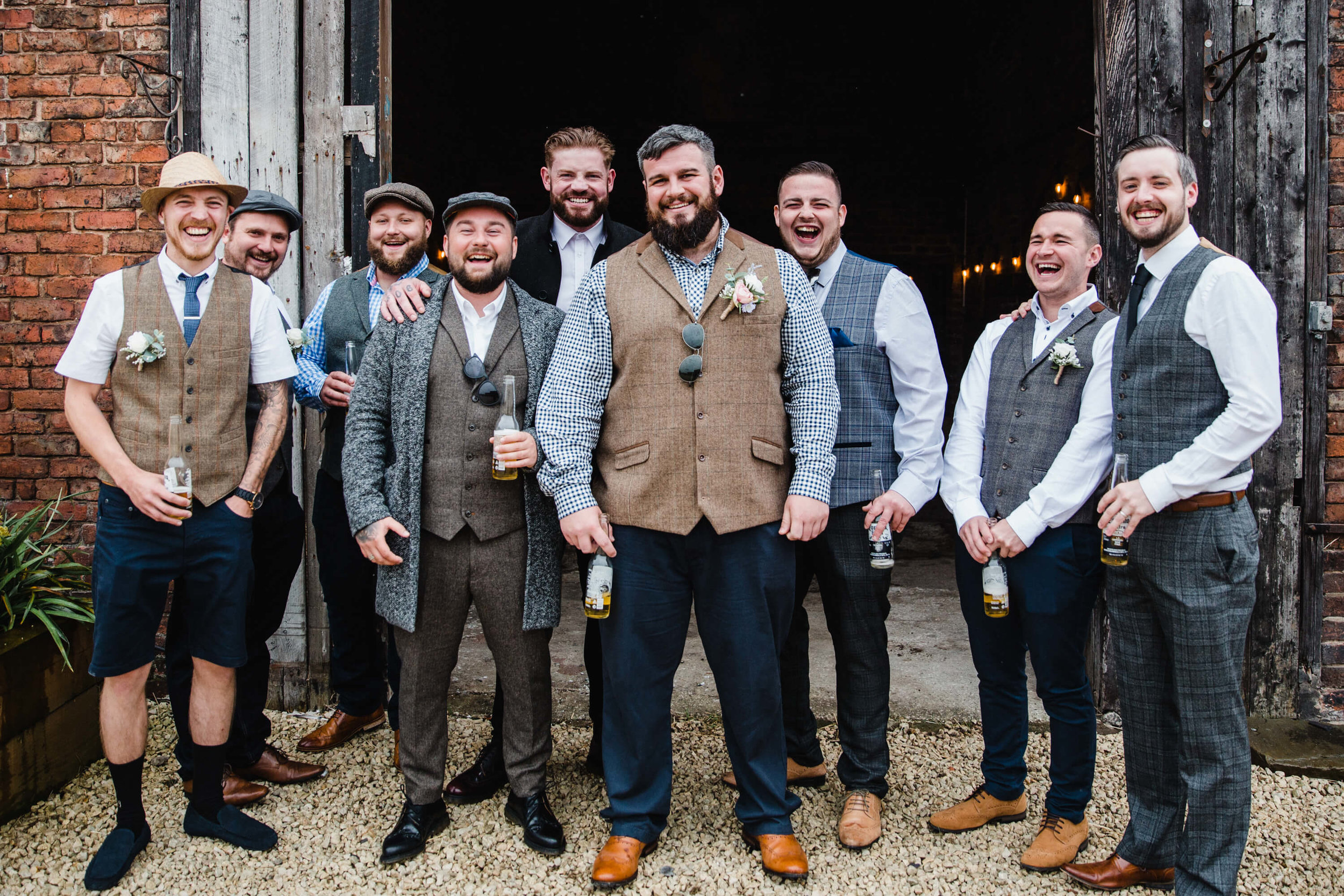groom and groomsmen smiling at camera before wedding service