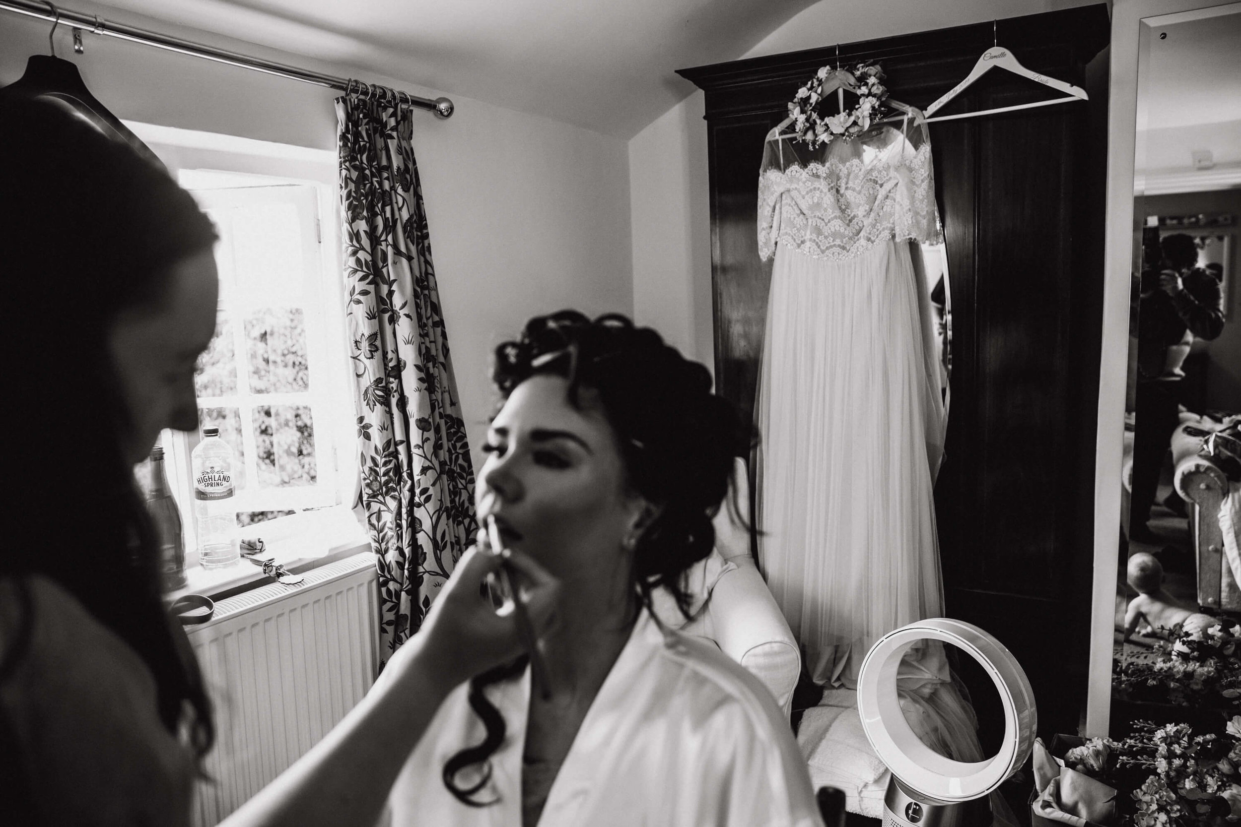 black and white monochrome photograph of wedding dress hung on cupboard