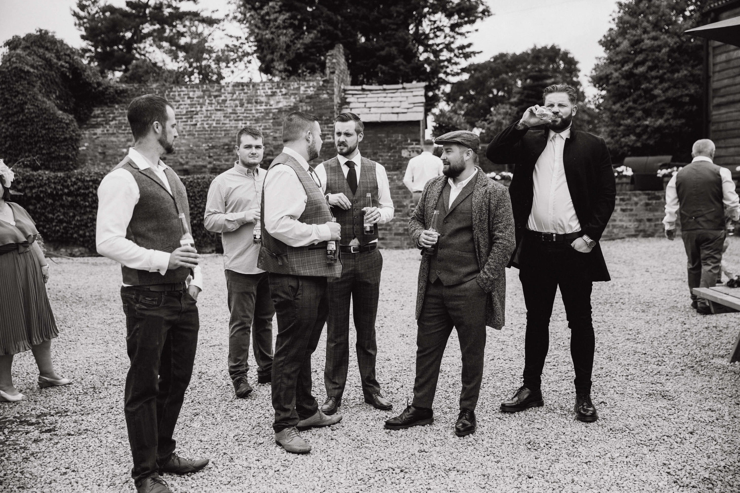black and white monochrome photograph of groomsmen in tweed waiting for ceremony