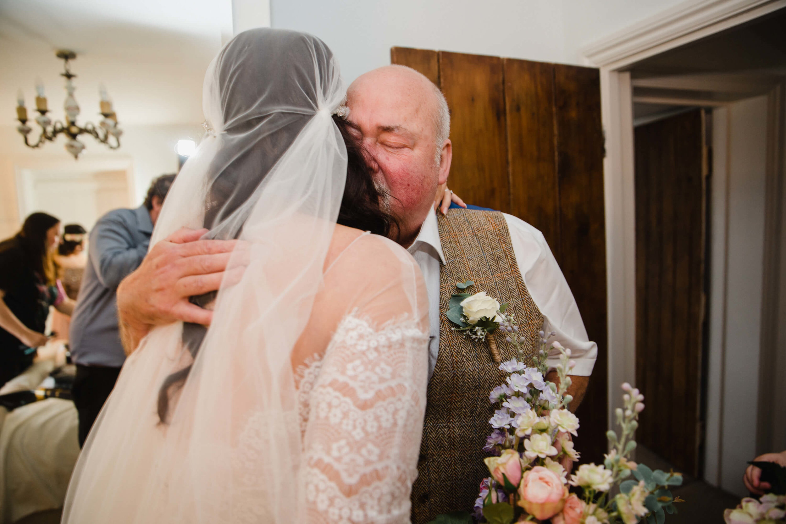 Father share hug with bride on stock farm estate