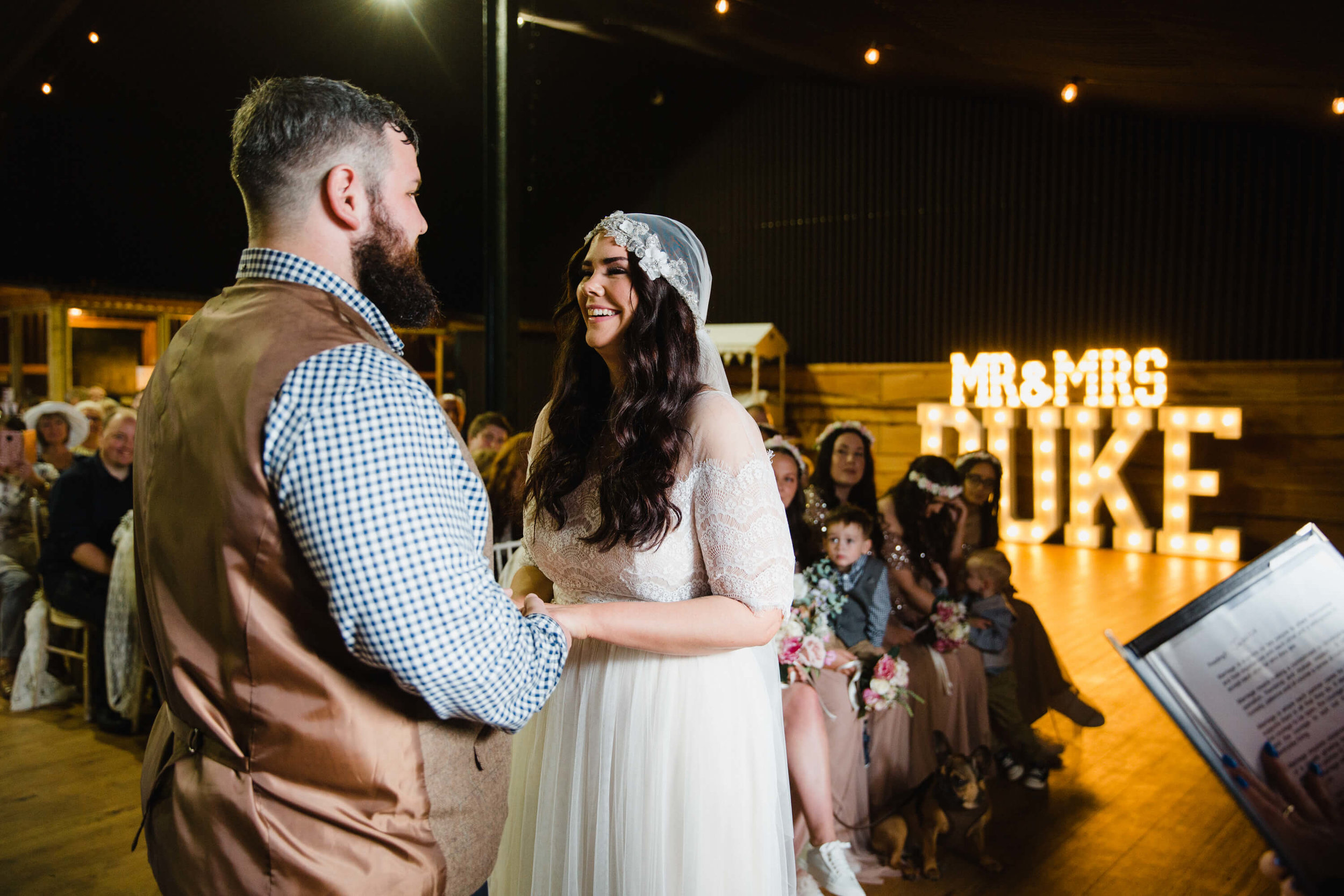 Newly wedded couple at top of aisle for nuptials with store light up letters in backdrop