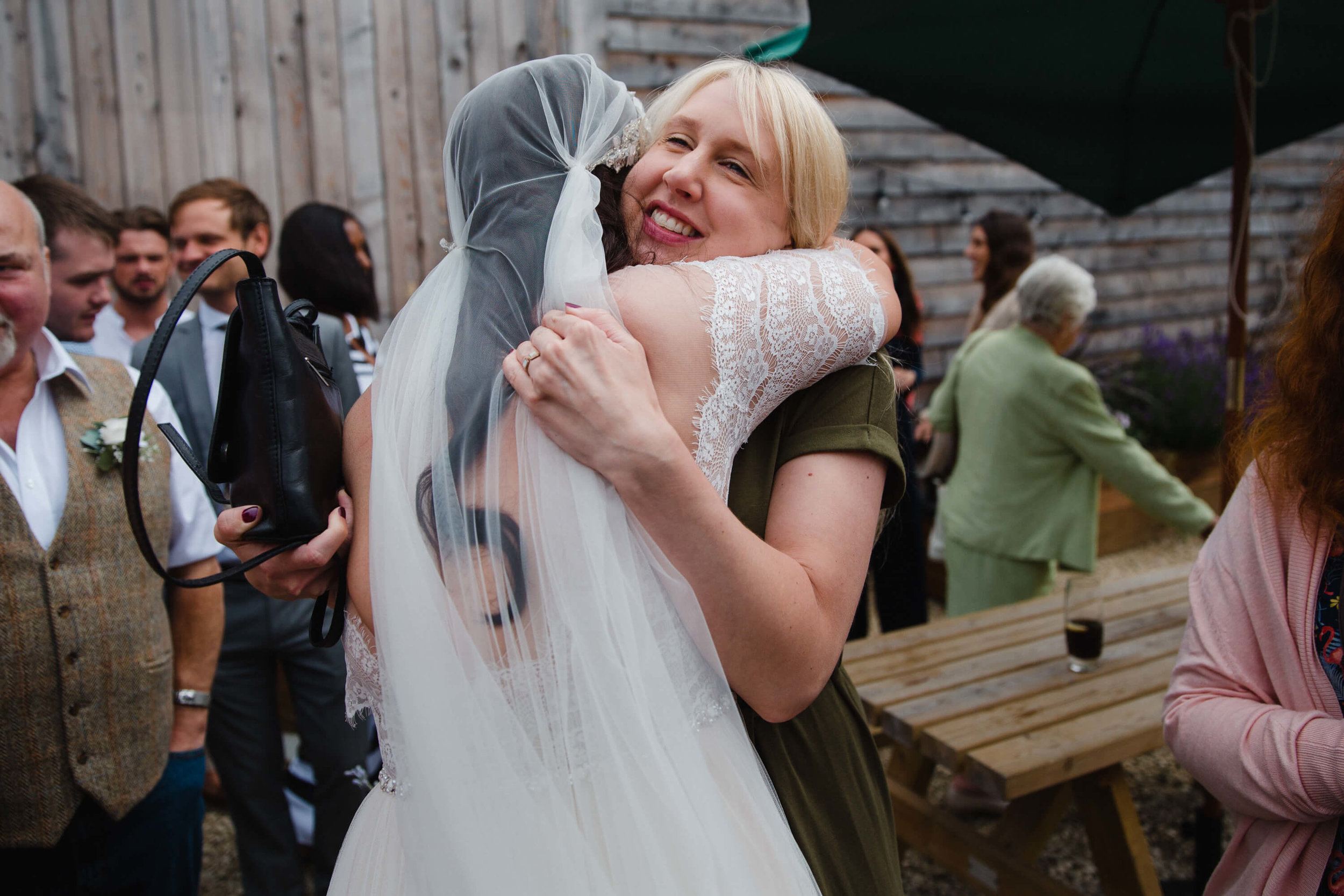 newly married bride shares intimate natural hug with guest