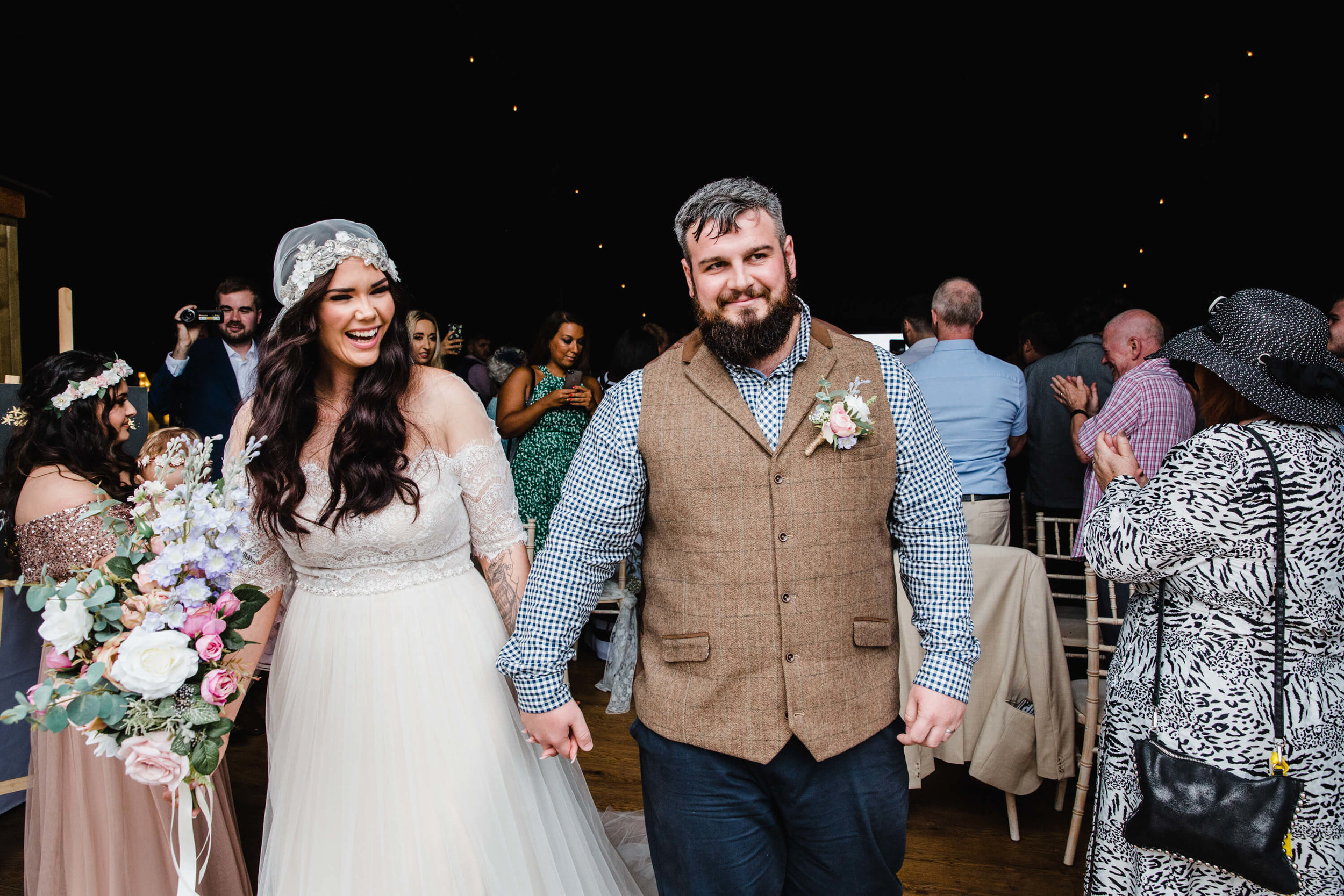 bride and groom hold hands after formal nuptial ceremony ends