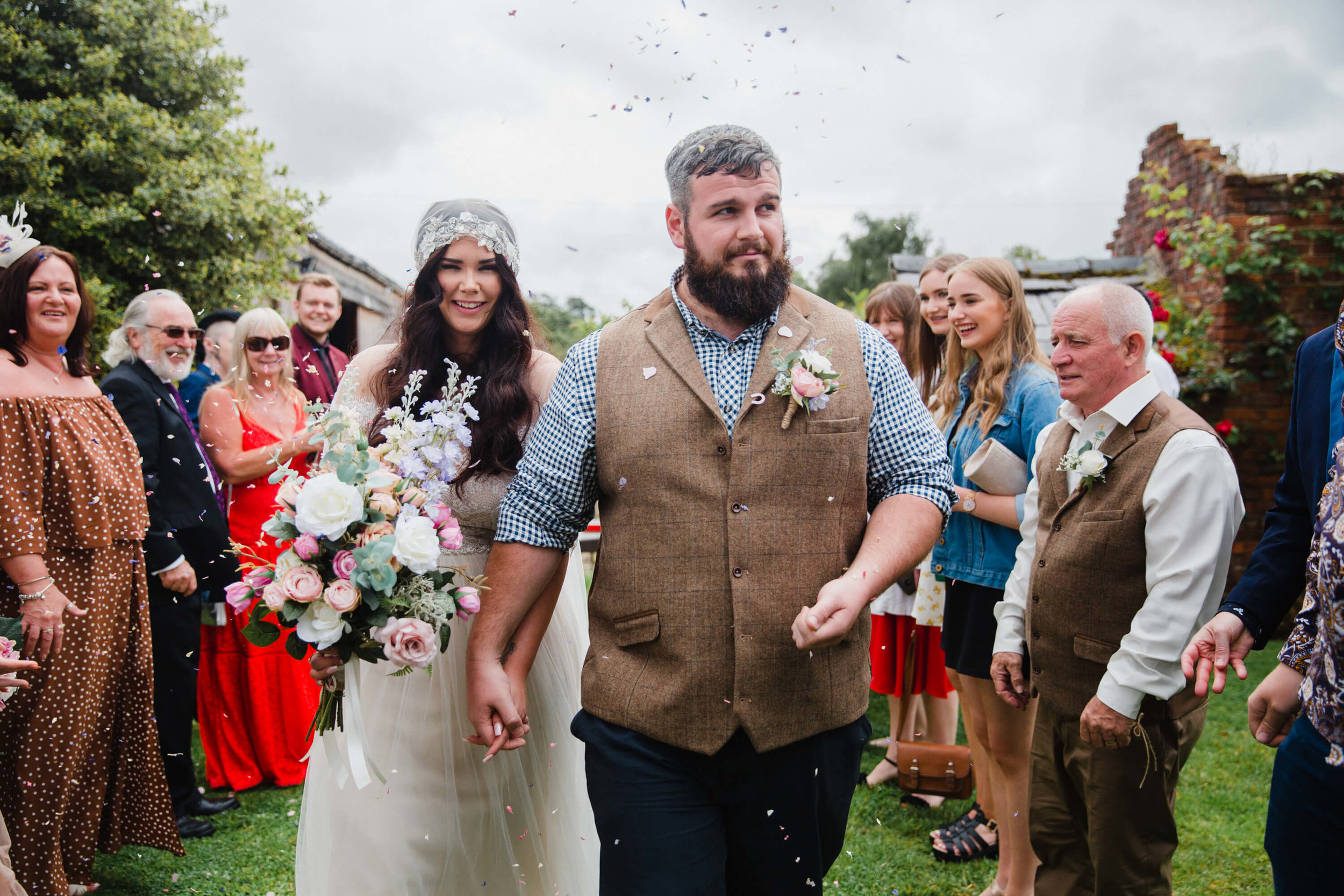 bride and groom step out into pastures for confetti throwing