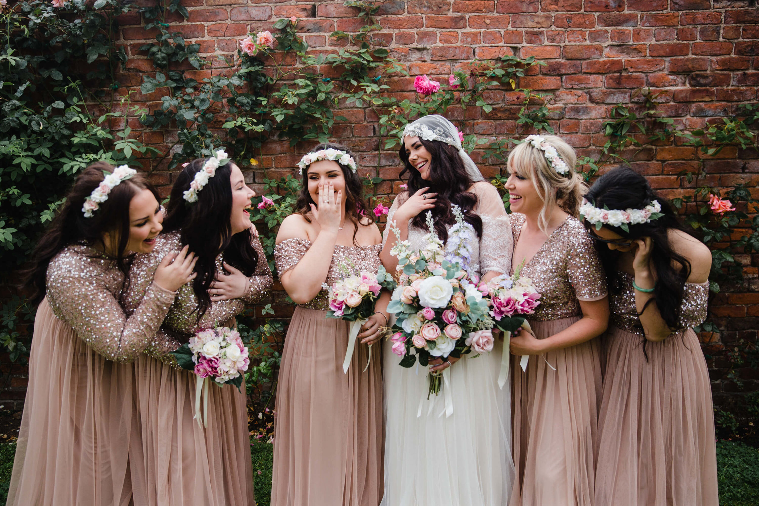 bride sharing a natural moment with bridesmaids while all holding bouquets