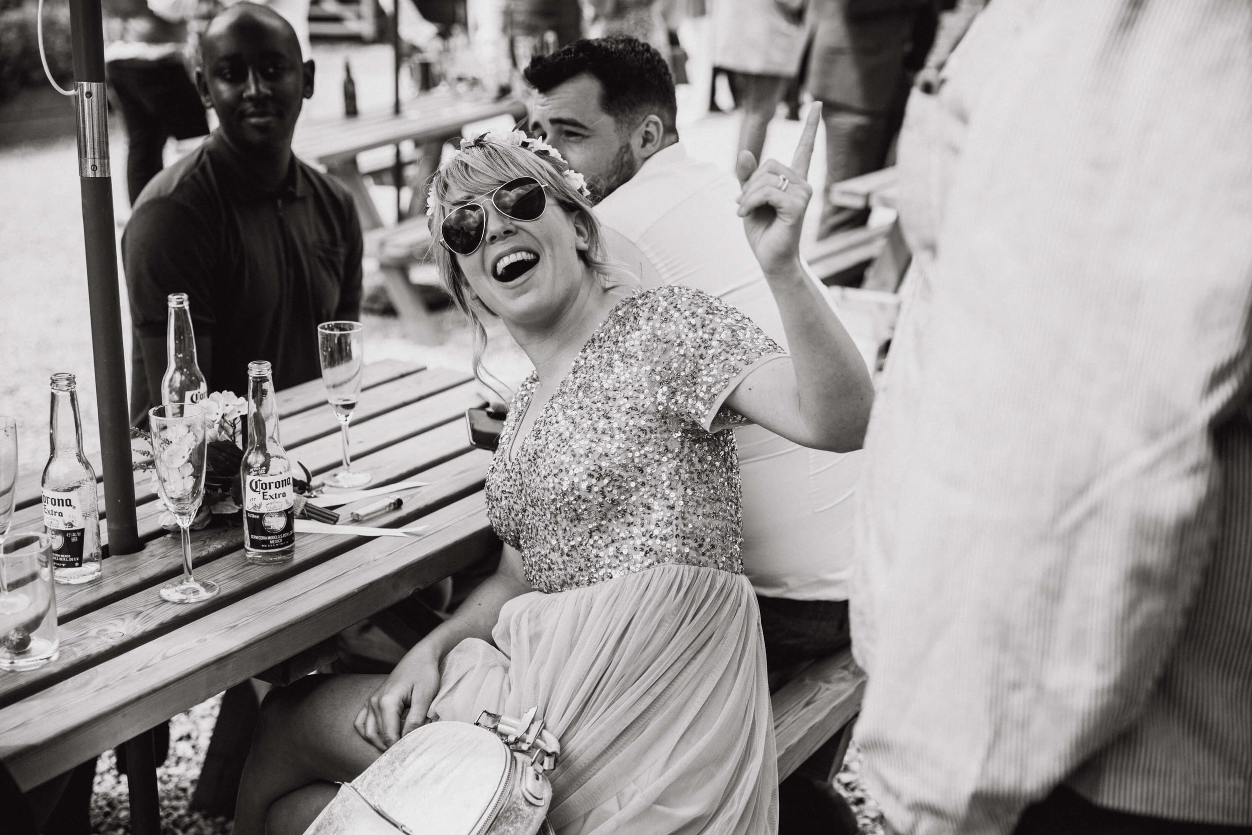 black and white monochrome photograph of bridesmaid in sunglasses laughing at guest