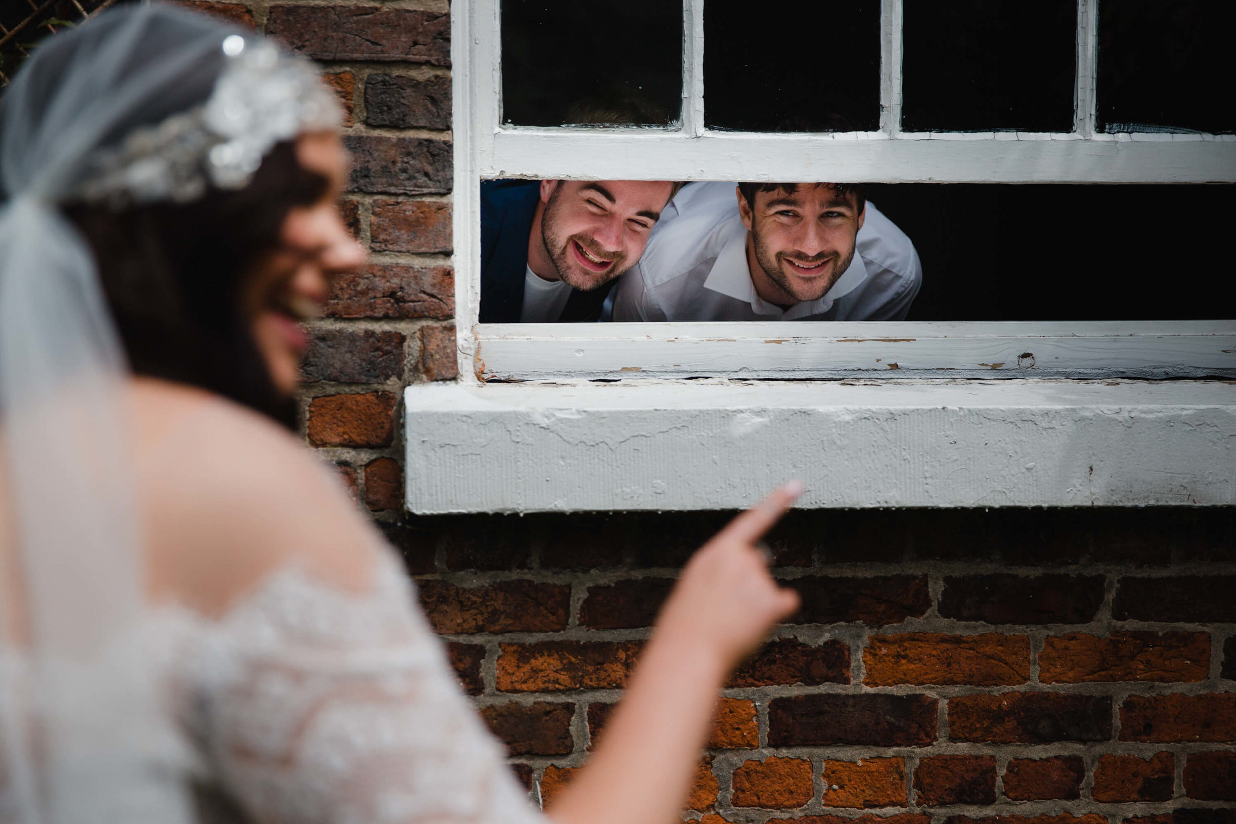 bride in foreground pointing at guests in window