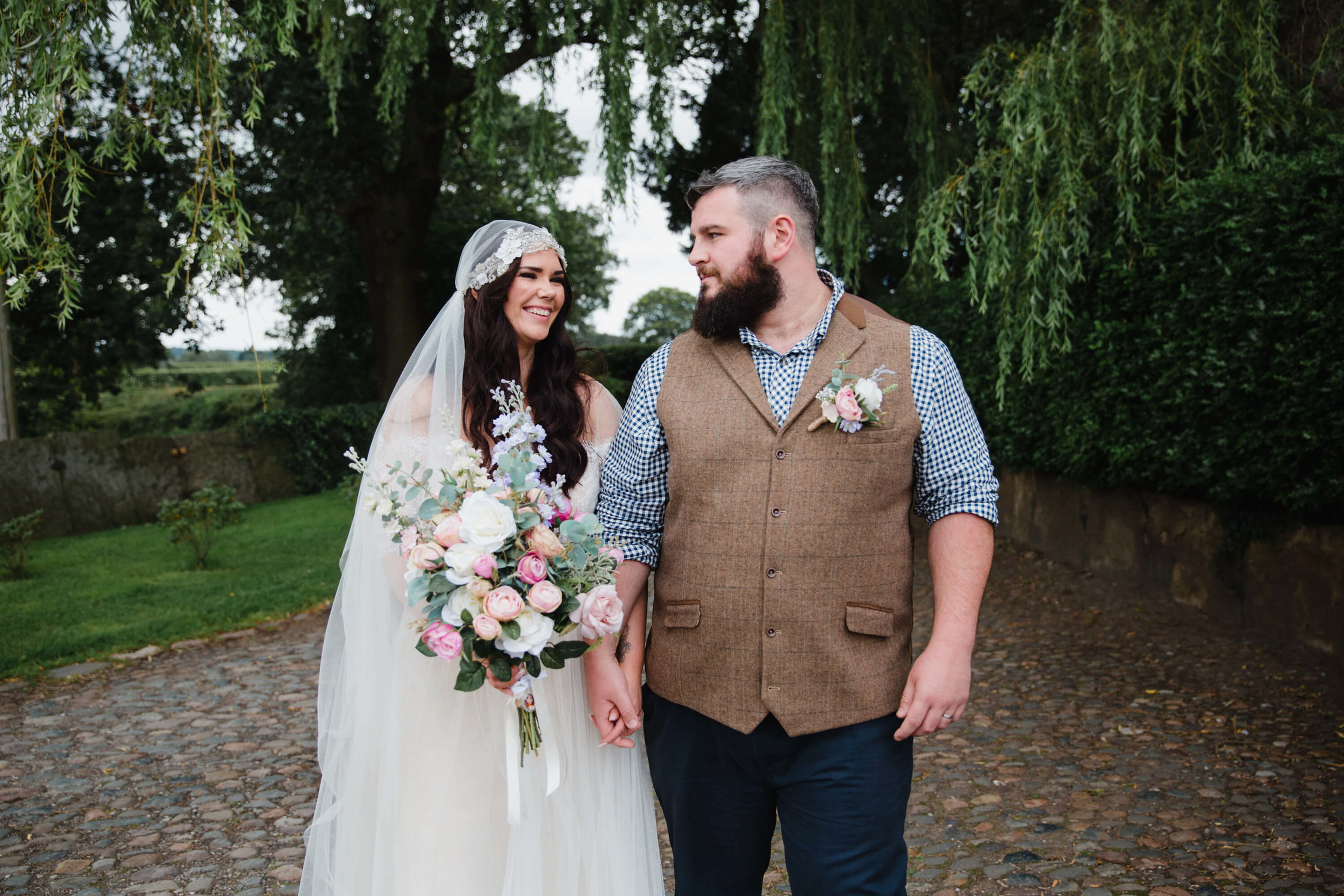 newlyweds take a stroll in cobbled orchard pathway
