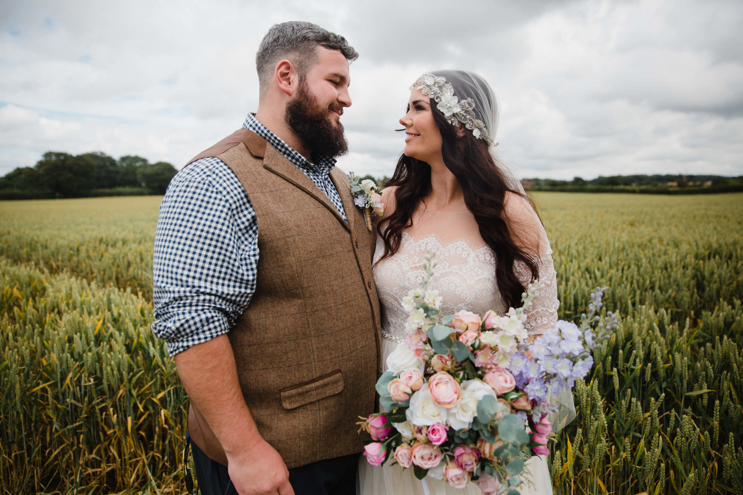 newlyweds sharing loving expression to one another in wheat fields