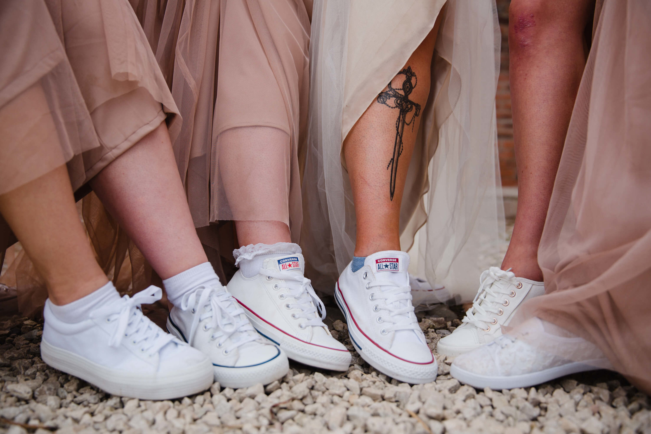 close up photograph of bridesmaids footwear white converse trainers