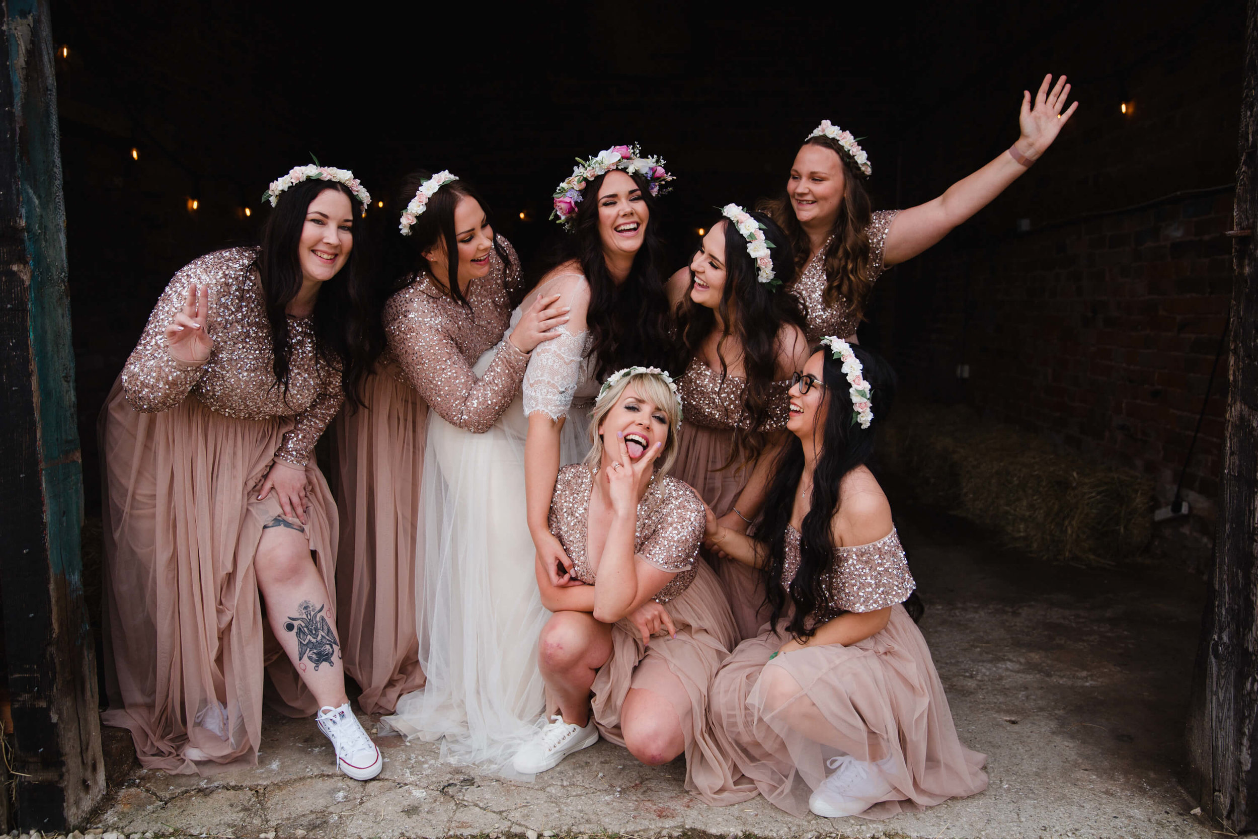 bridesmaids pose together for camera at entrance to farm homestead