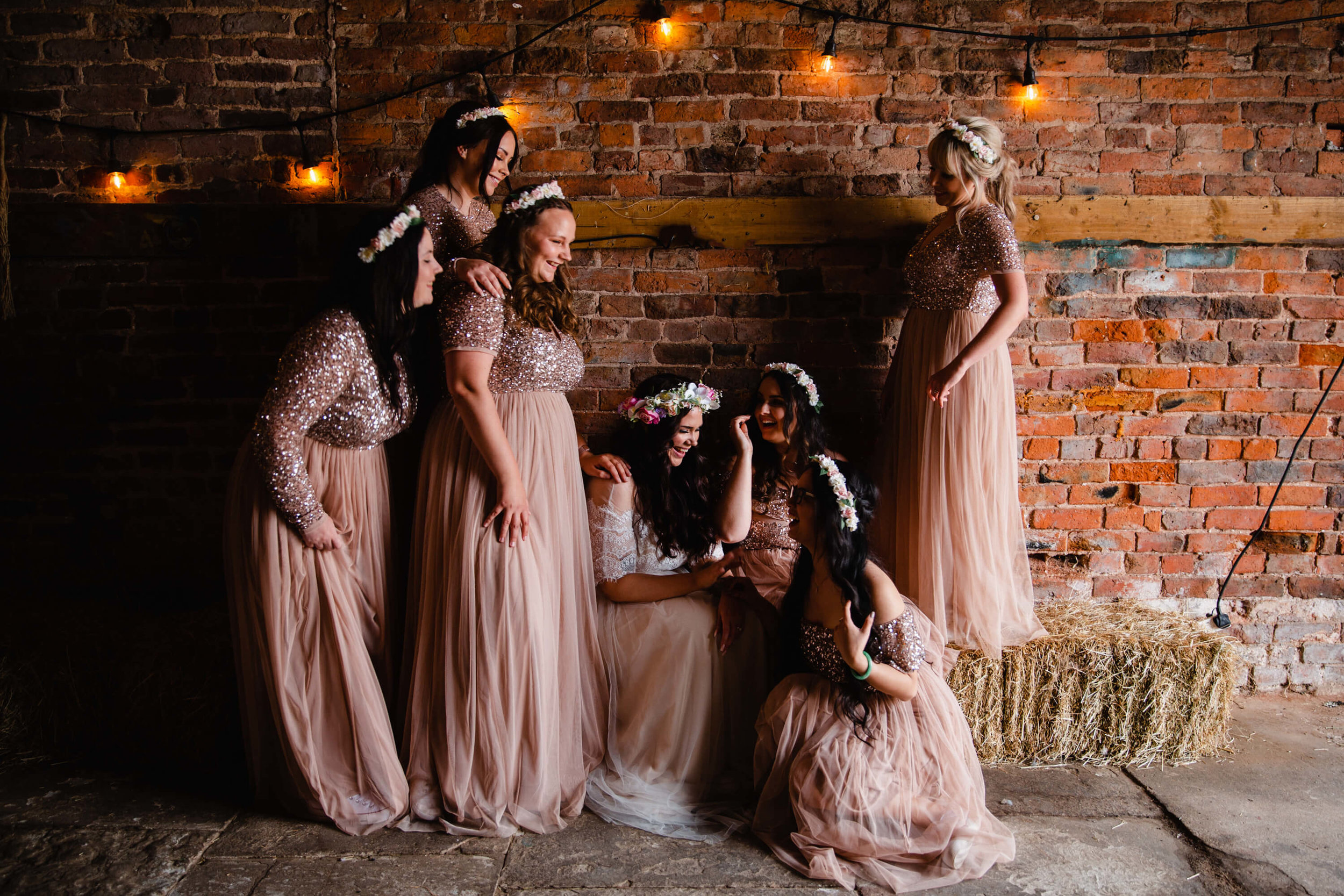 bridesmaids gather on hay bales lit up in natural light and festoon bulbs