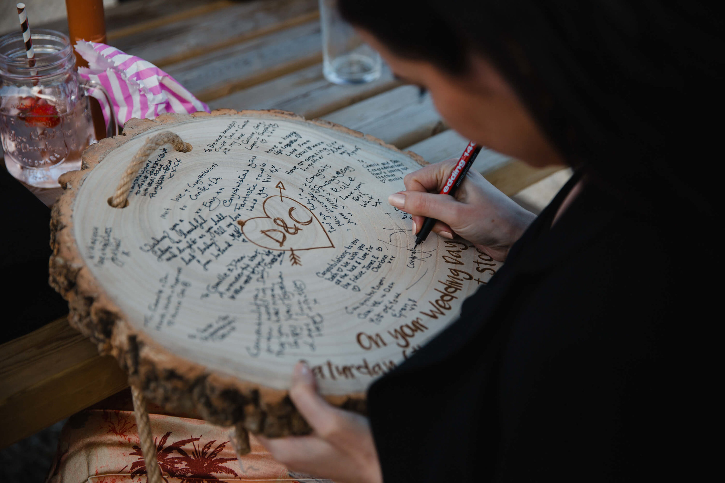 wedding guest writing on to wooden tree ring