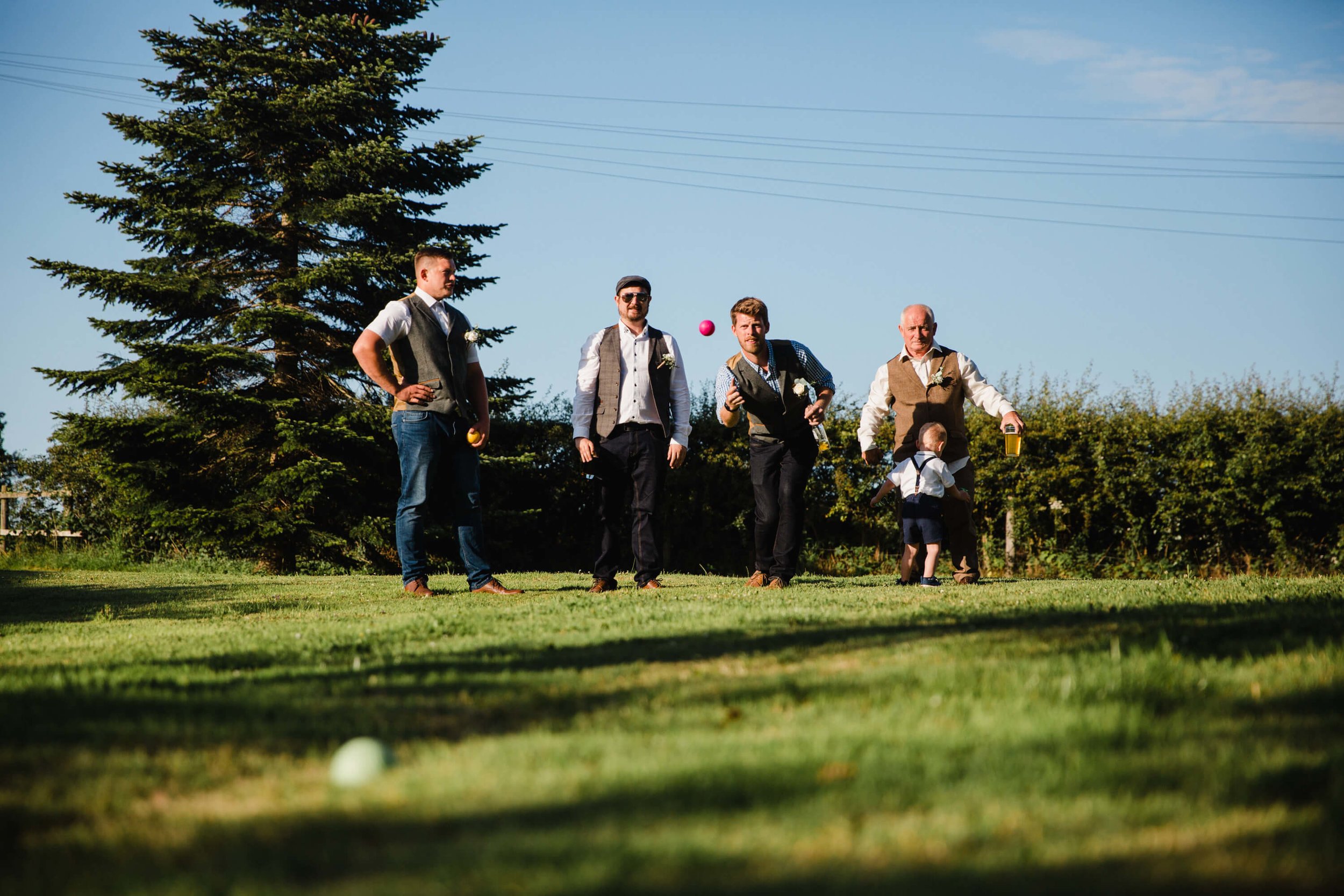 photograph of groomsmen playing lawn boules in pasture