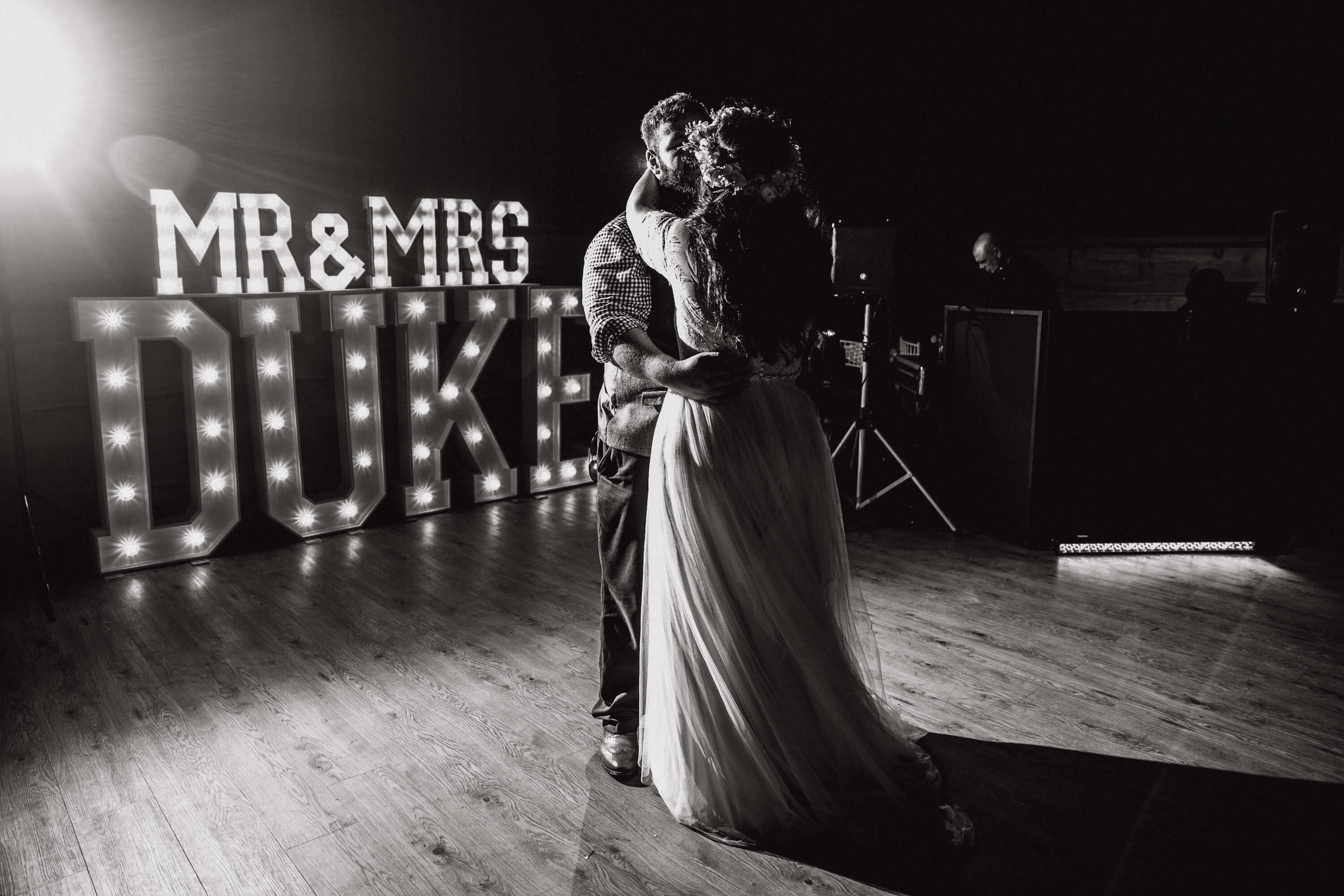 monochrome photograph of first dance and light up lettering