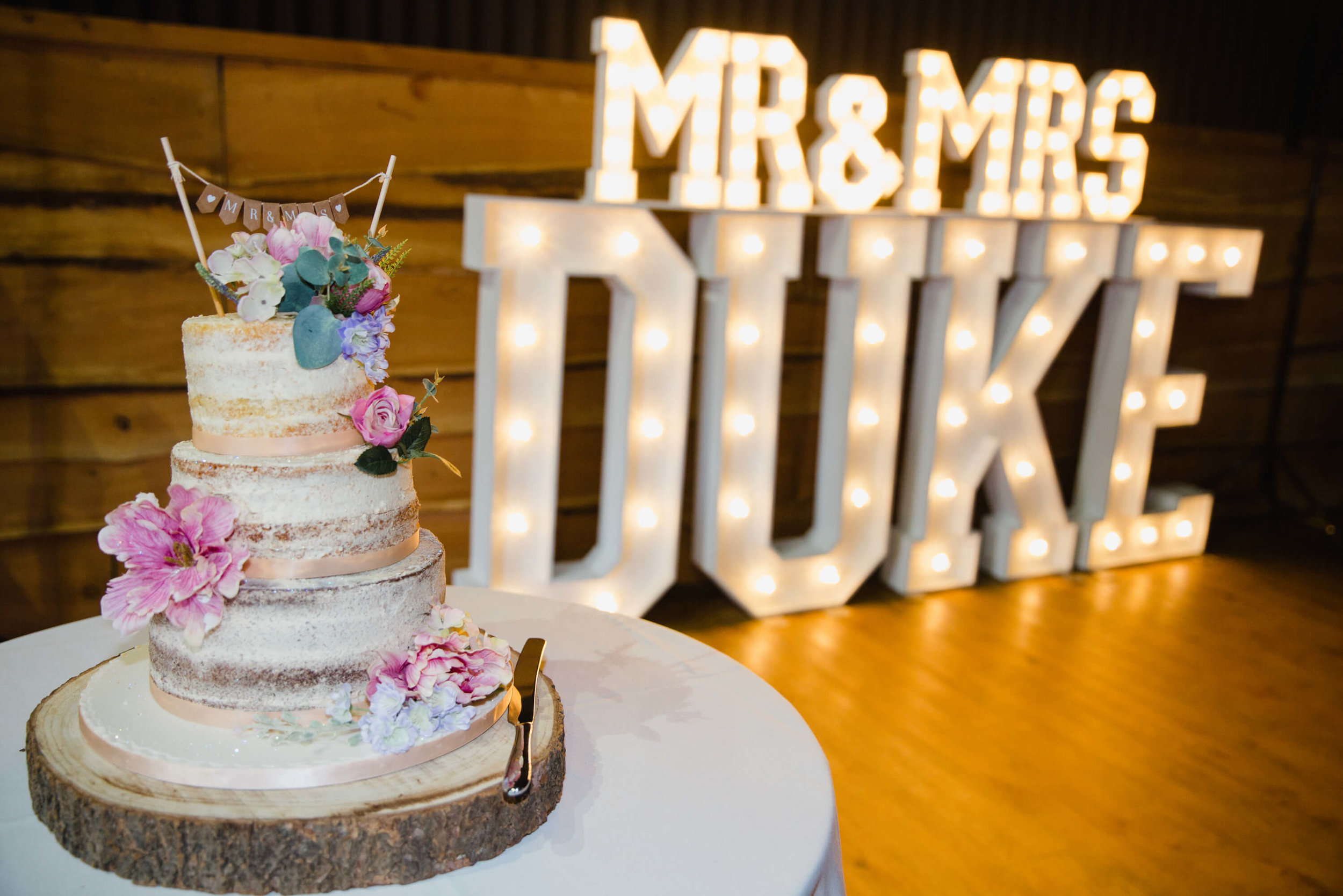 wedding cake with light up lettering in backdrop
