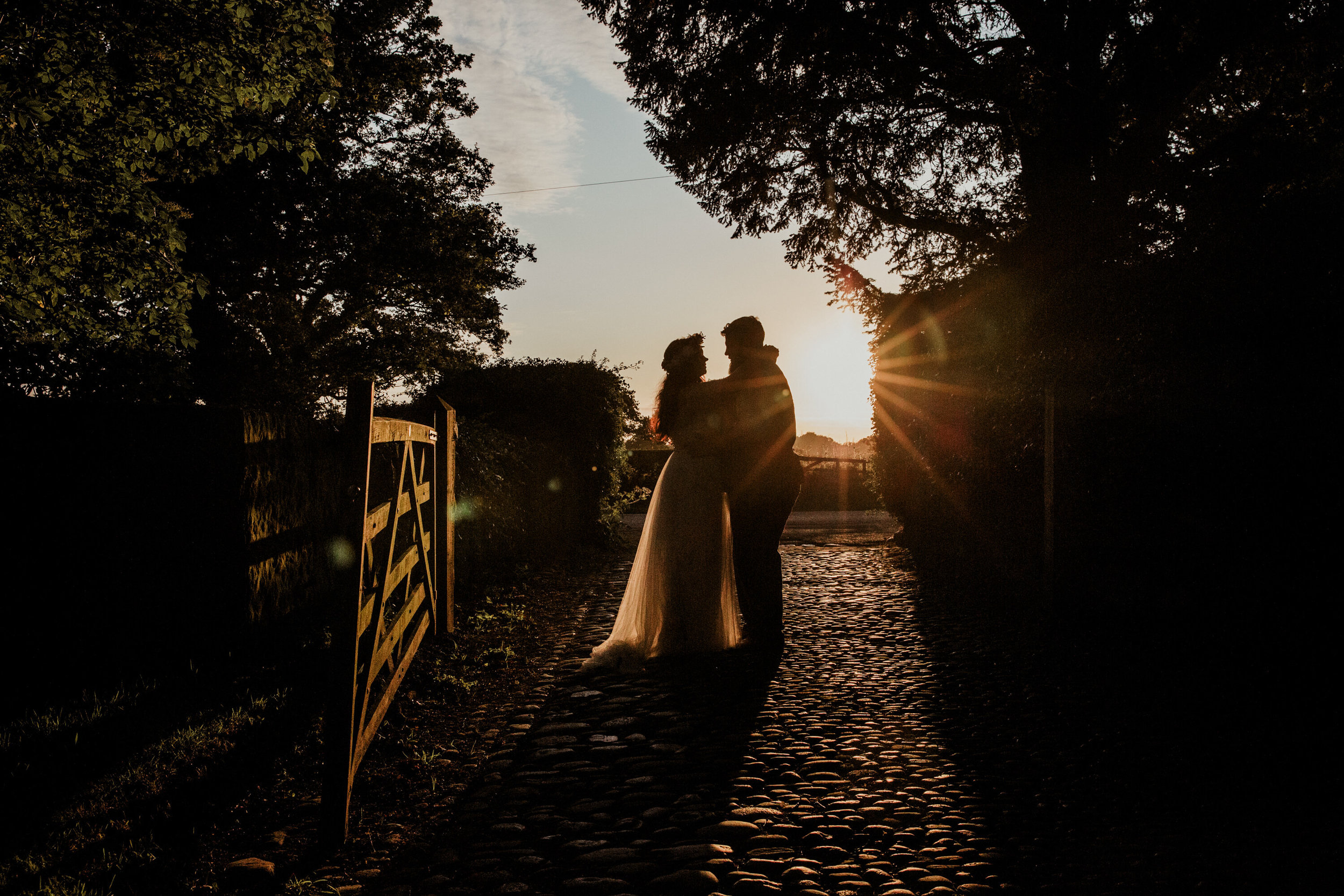 sunset portrait of bride and groom silhouette on cobbled path at Stock Farm wedding venue