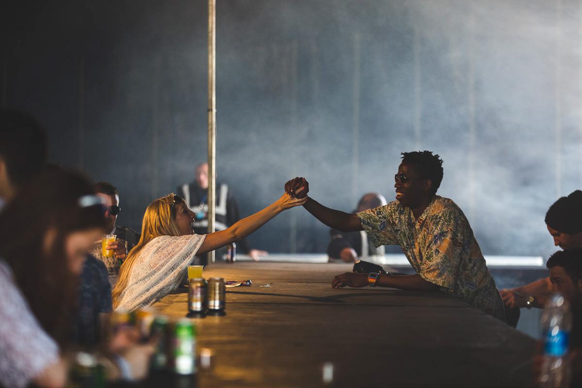 Bar tender and festival goer shake hands over the bar