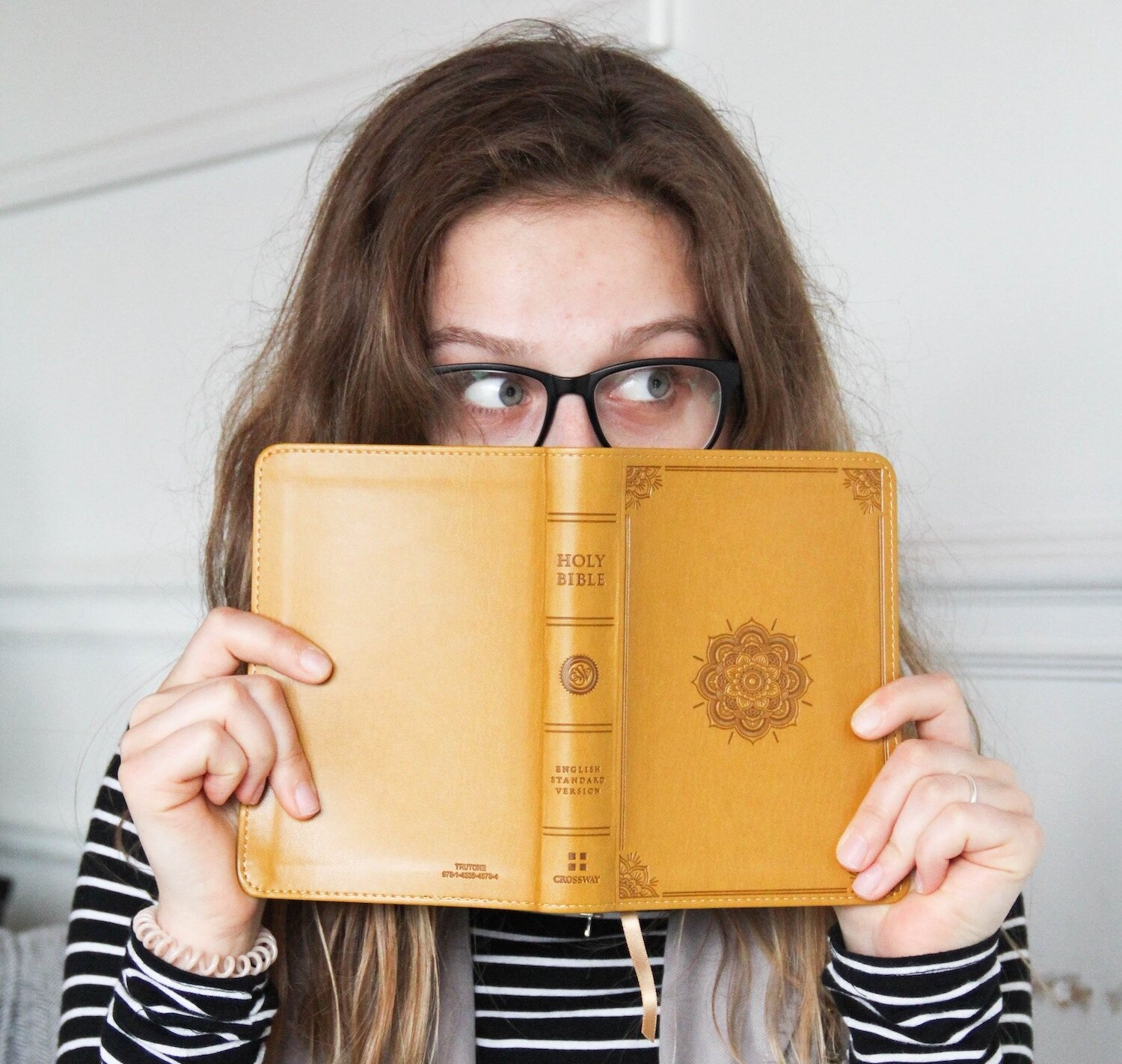 girl holding up yellow bible in front of her face.jpg