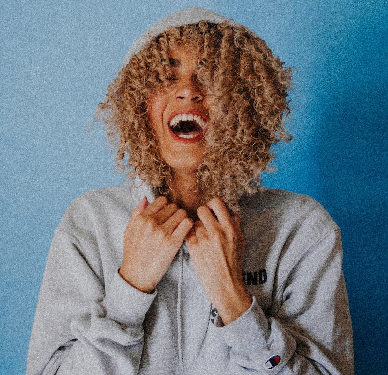 smiling woman against a blue wall.jpg