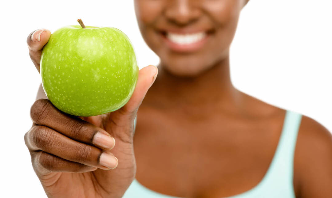 african american woman holding out a green apple