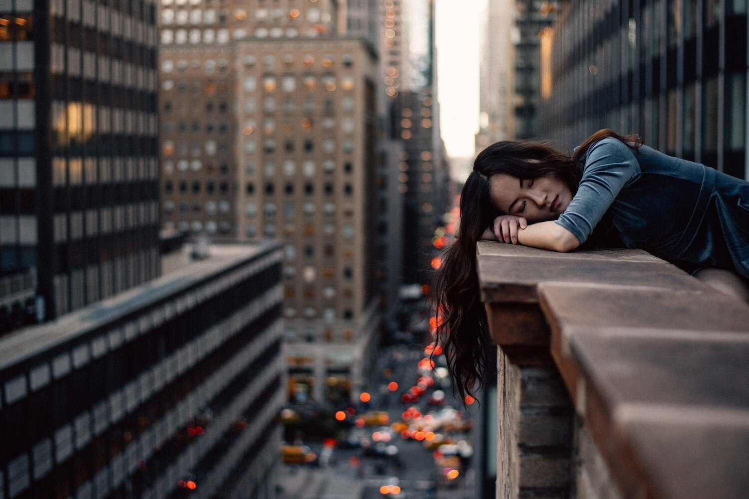 woman lying with her head on the ledge traffic in the background.jpg