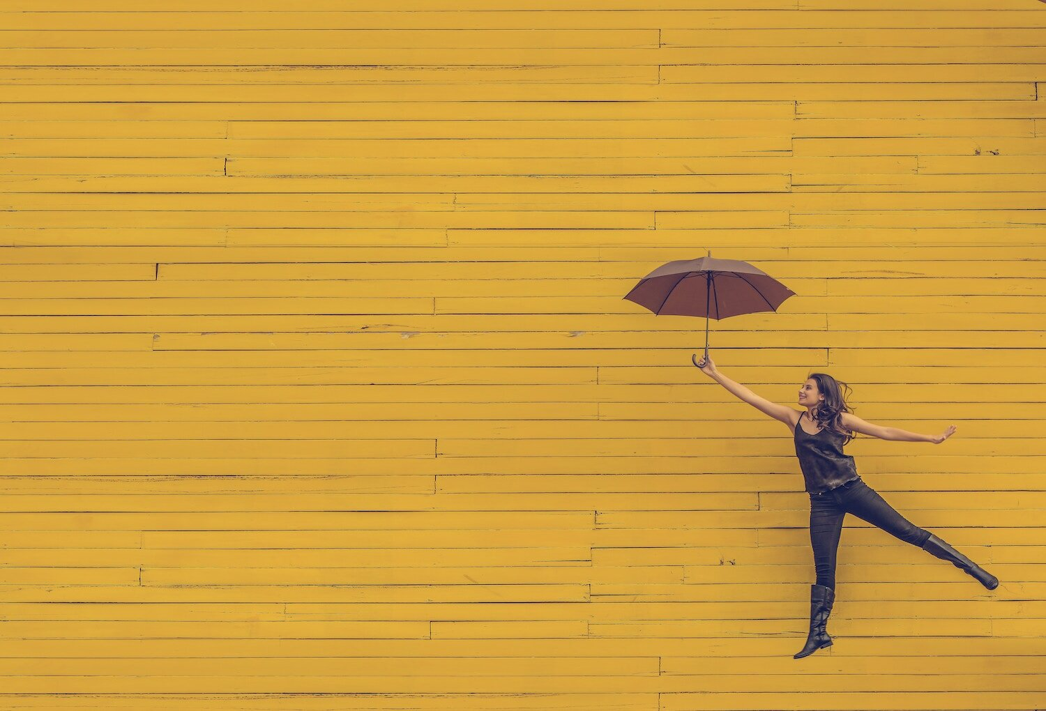 young woman floating in the air with umbrella againt yellow background.jpg