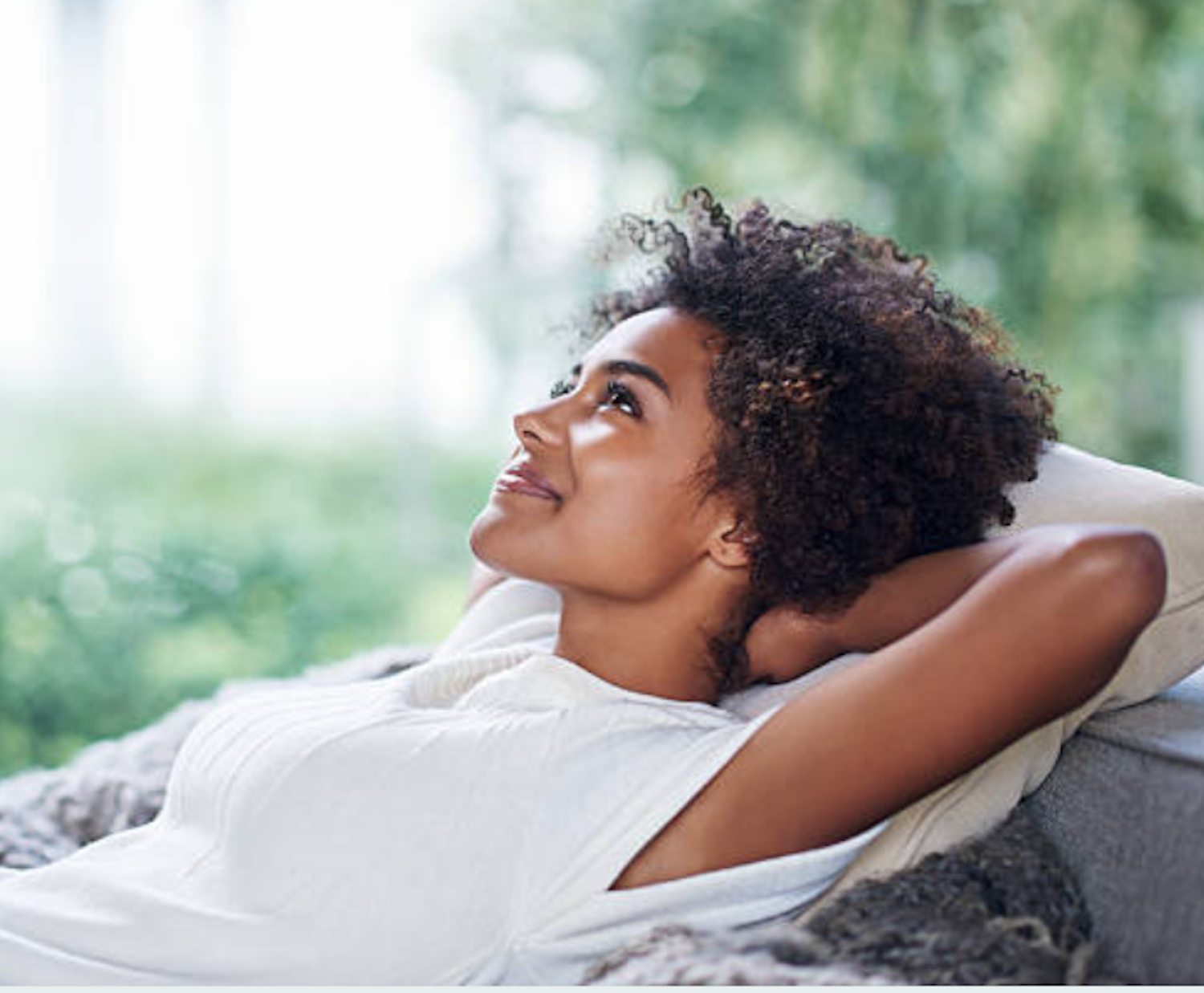african american woman with curly hair resting with hands behind her head and smile on her face