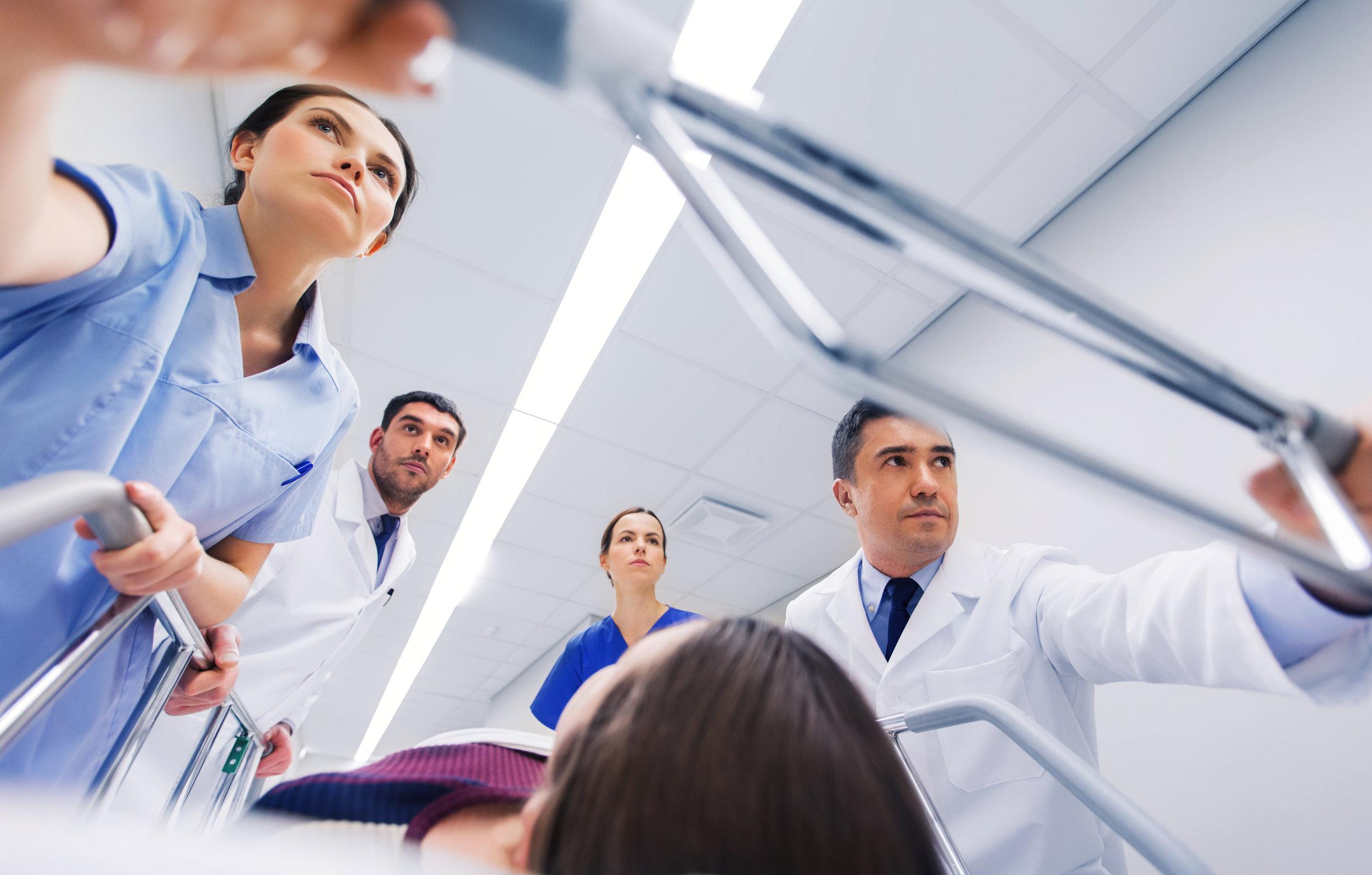 medics-with-woman-on-hospital-gurney-at-emergency-PFY8TVD.jpg