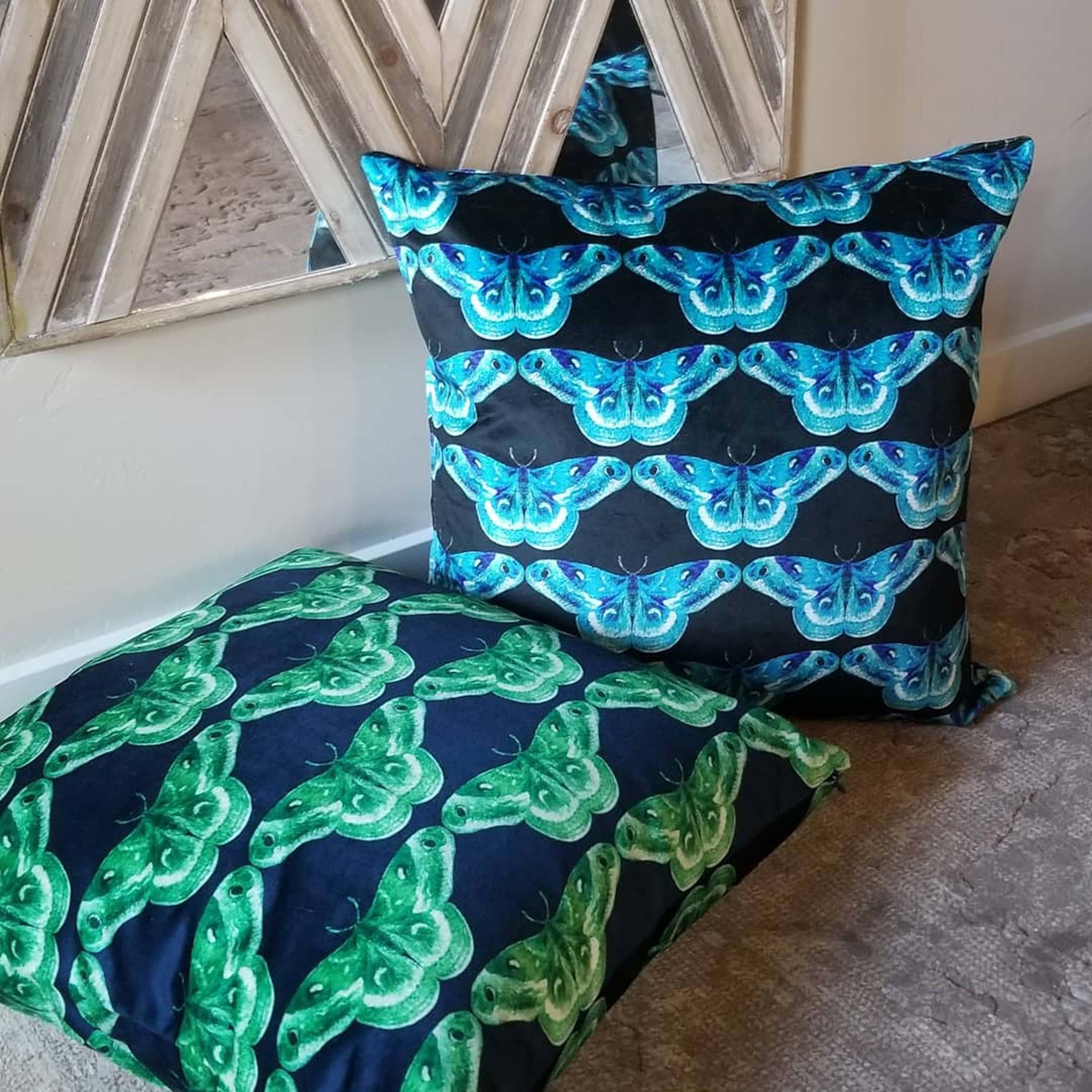 Set of black pillows with green and blue printed butterflies