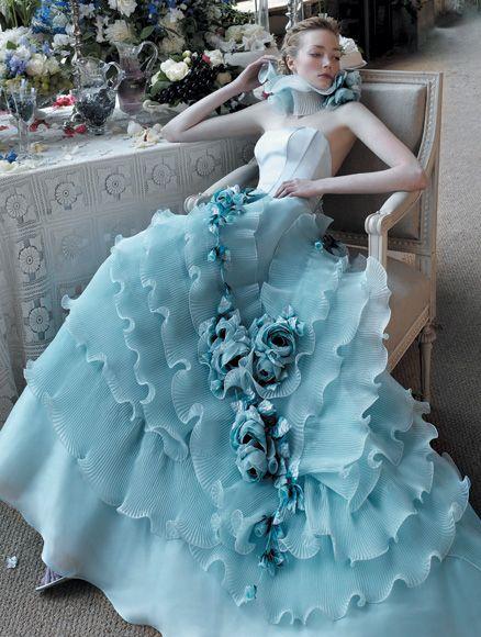Beautiful woman sitting on wooden armchair wearing a blue wedding dress