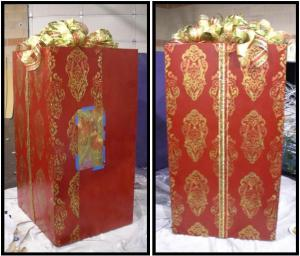 A present with color red wrapper and gold ribbon