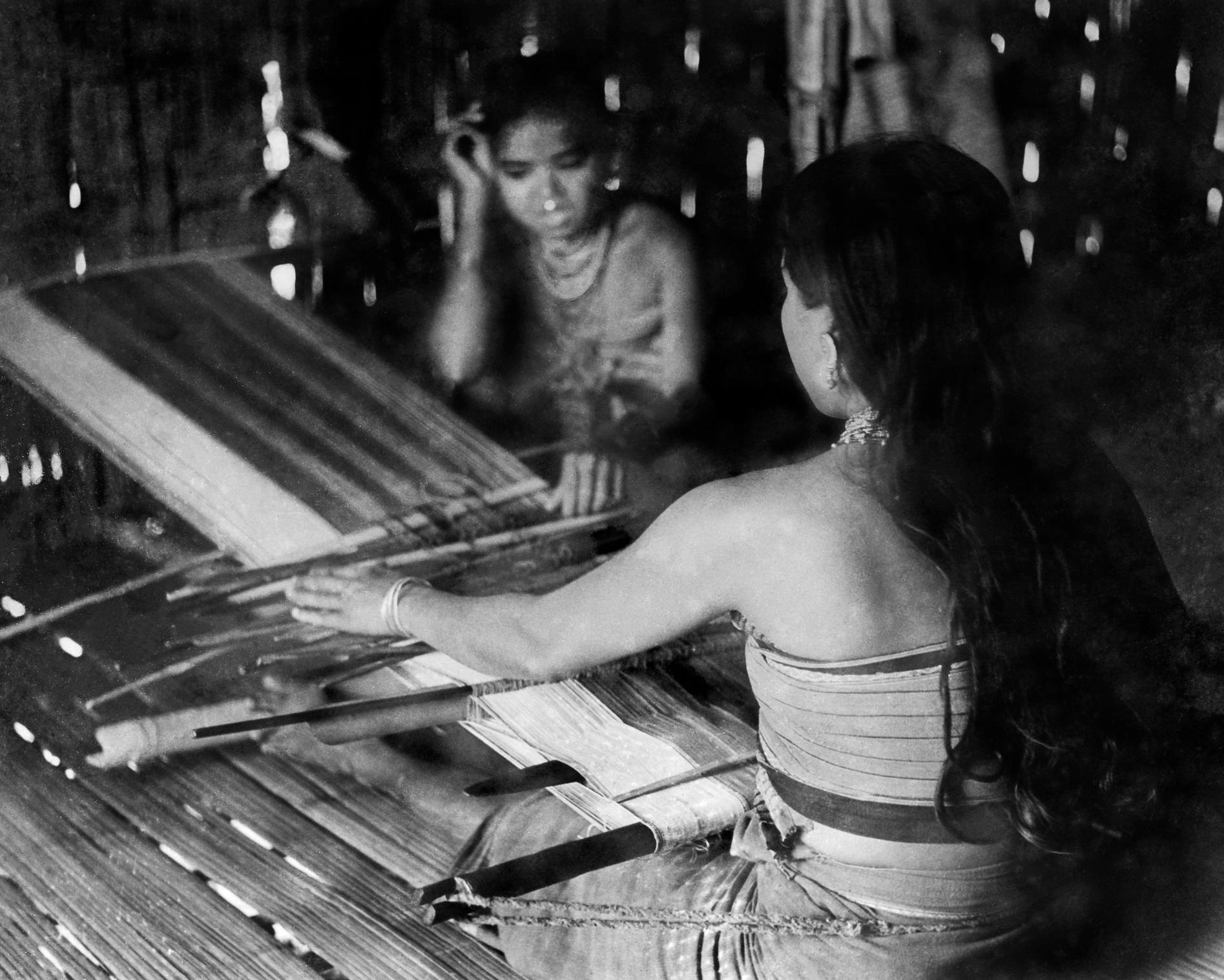 Tripuri woman weaving one half of a Rignai (traditional wrap skirt) with a white border on a  ri thanti , or backstrap loom.  c.1974