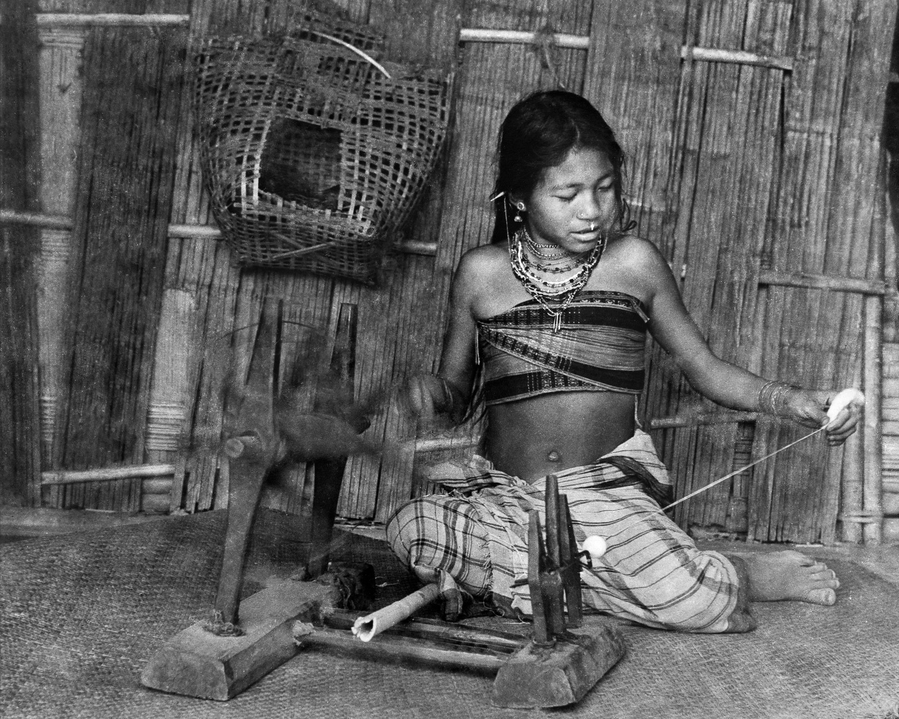 Young Jamatia girl spinning cotton, seated on a finely plaited bamboo mat called  yang khum  or  sital pati . Girls start learning how to weave very young, around 10 years of age.  c.1974