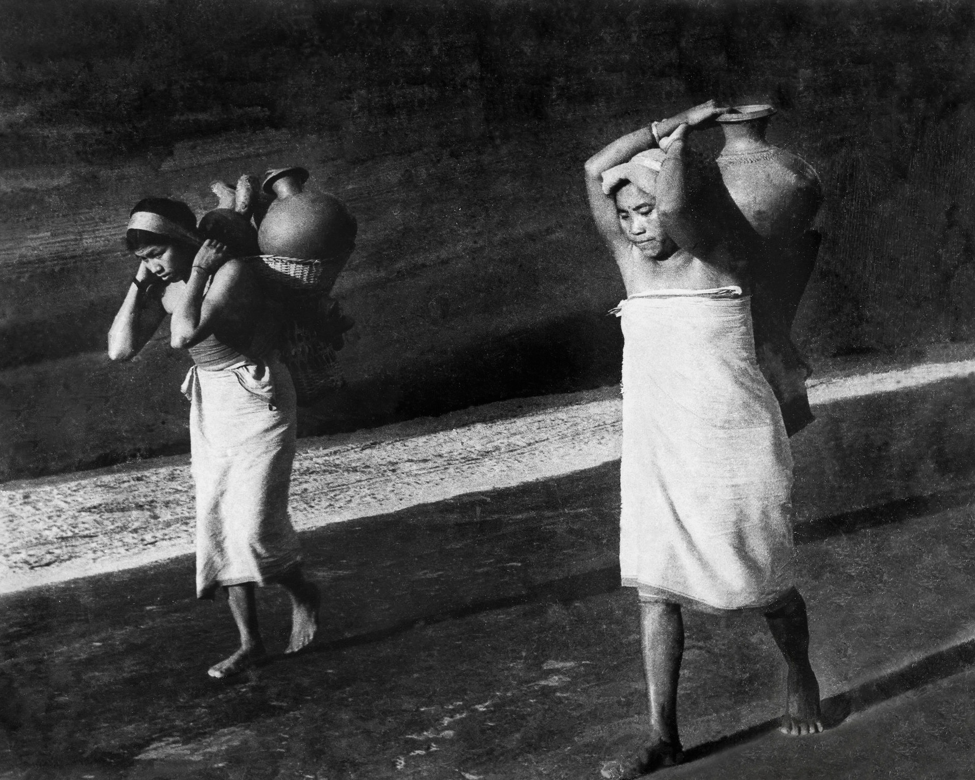 Women from the Deb Barma tribe wearing simple white  pasras  (wrapped lower garment) carrying water back in clay pots to their village near Teliamura.  c.1977