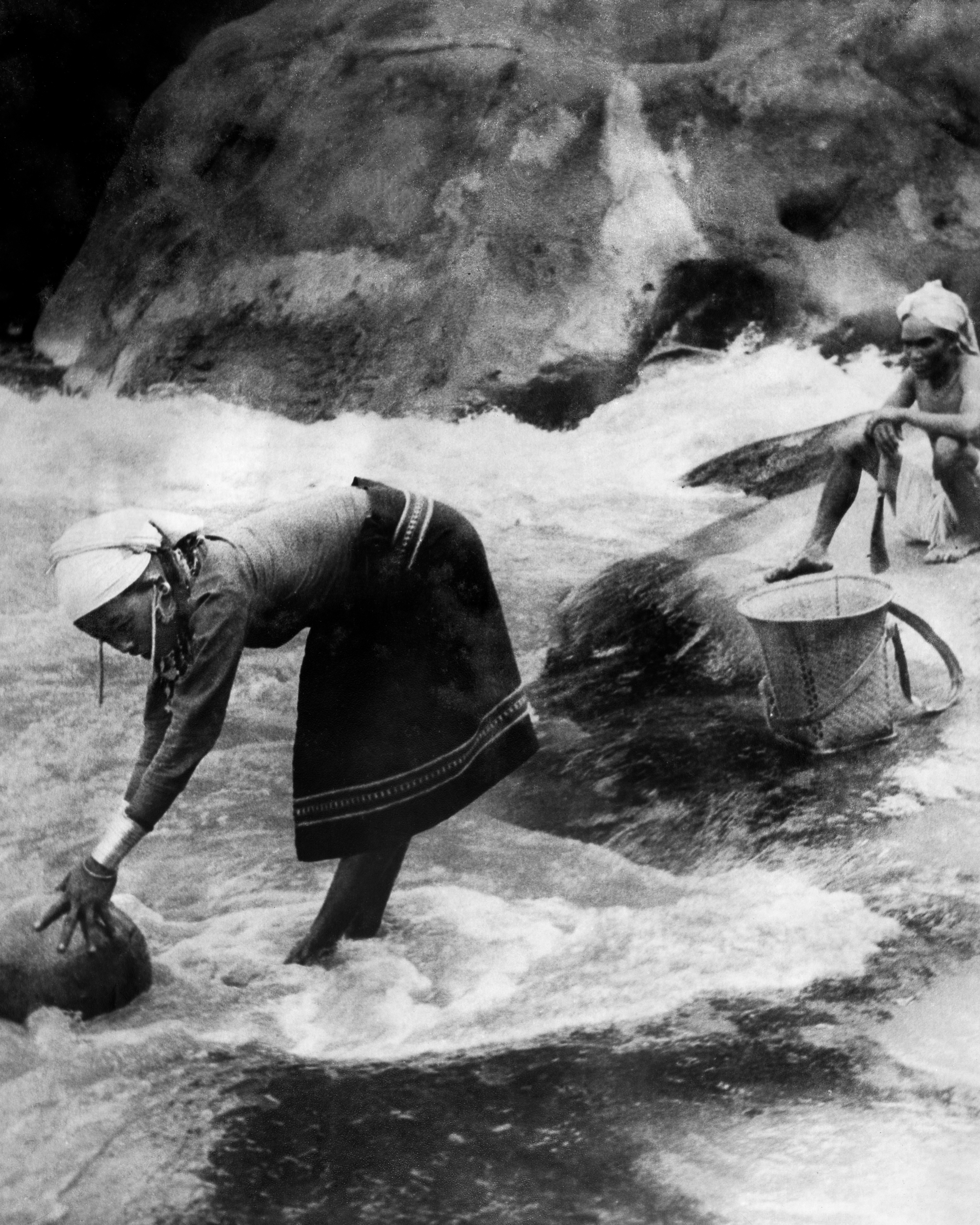 Reang couple fetching water from a nearby river. The woman is wearing a plain  rignai  with patterned borders and traditional jewellery.  c.1974