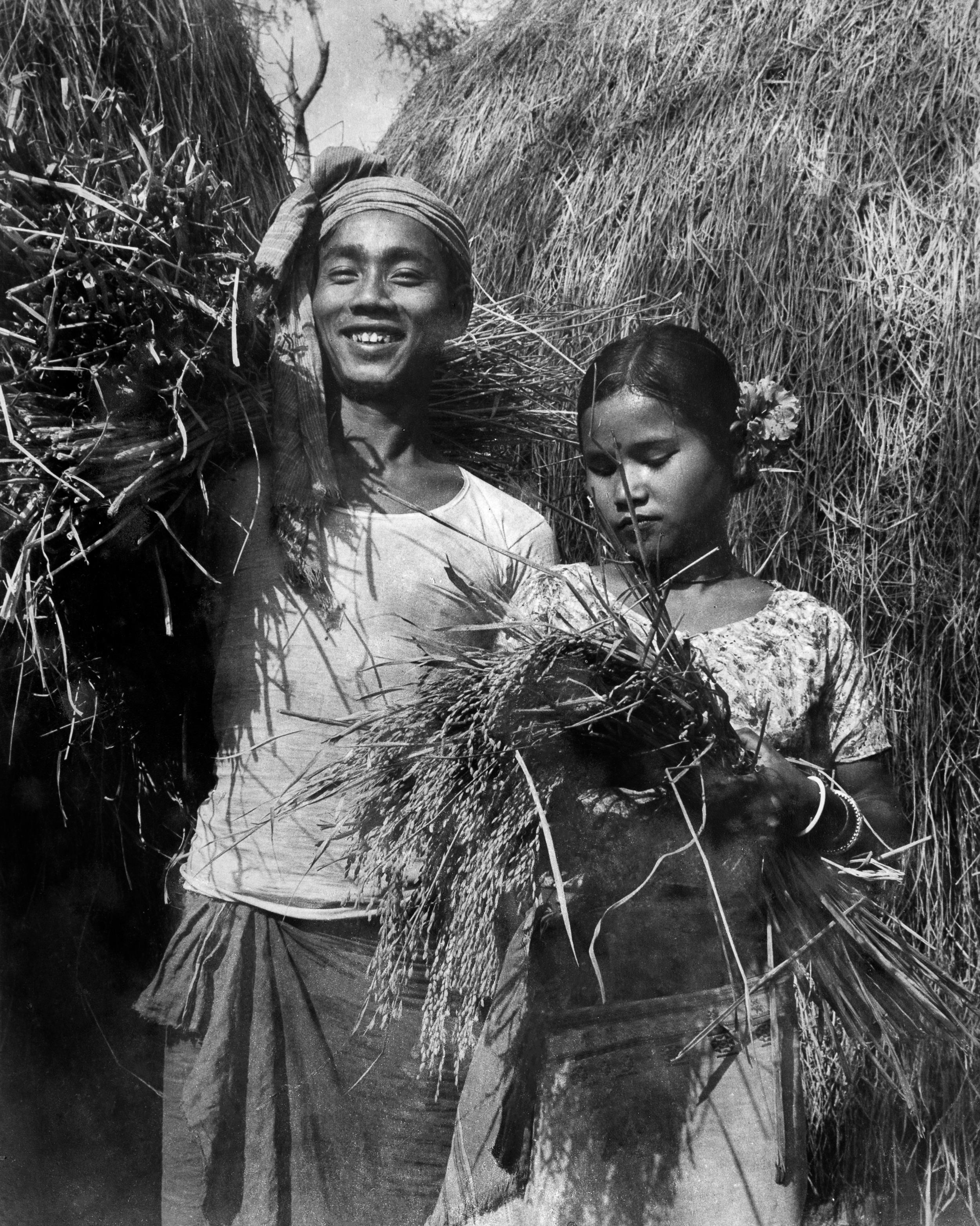 Mogh couple during harvest season with paddy collected from their rice fields. The woman wears a screen printed short blouse instead of a risha.  Maitang  or paddy is a common motif in Tripuri textiles.  c.1977
