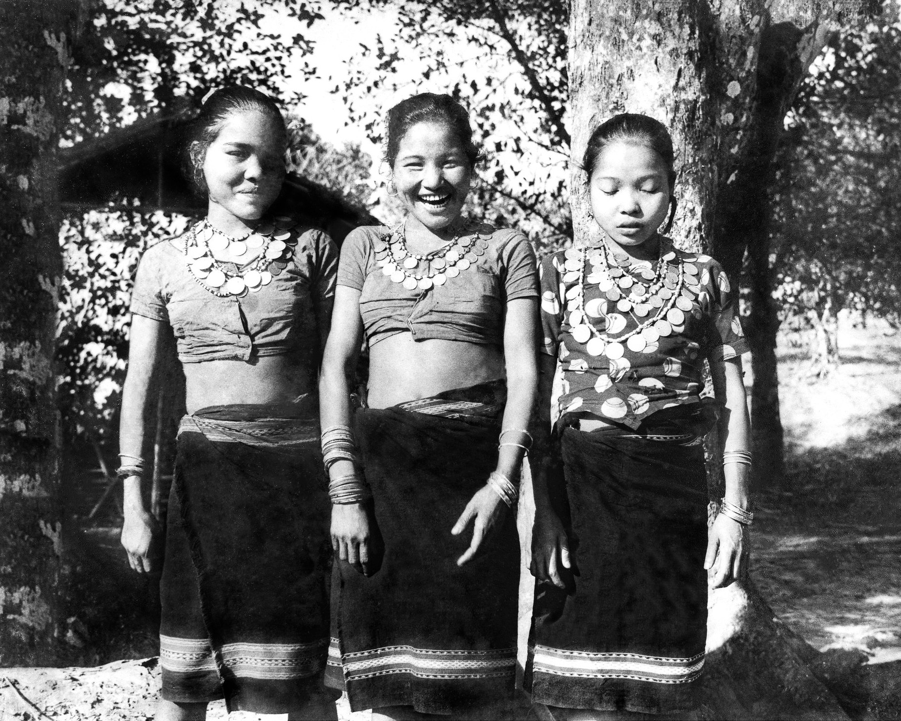 Reang girls wearing traditional  rignais  with stitched blouses. It is still common for Reang women to wear coin necklaces as a part of their everyday attire.  c.1978