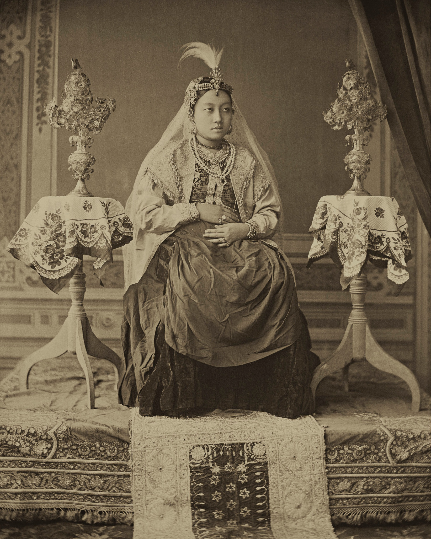 Maharani Monmohini Devi. The Maharani posing like British Queen Victoria in what appears to be an eclectic and creatively staged shot. The Queen wears a plain European dress with one of her own blouses, a silk jacket with long sleeves and a feathered Mughal head ornament that holds a veil down in place.  c.1890.  Photographed by Raja Bir Chandra Manikya. Platinum palladium print.