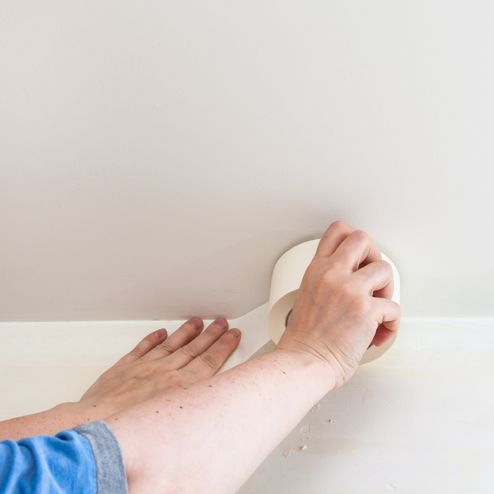 painter-fixes-sticky-tape-on-wall-before-painting-P4XN9CR.jpg