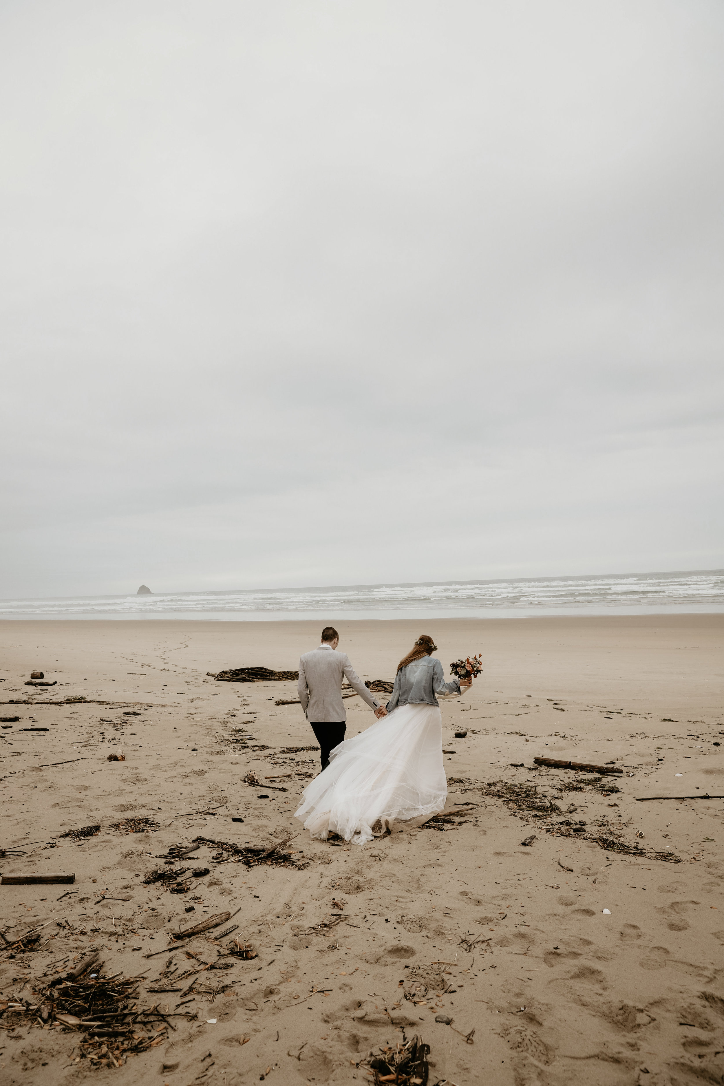 bohemian couple walking on beach during elopement holding custom floral bouquet.jpg