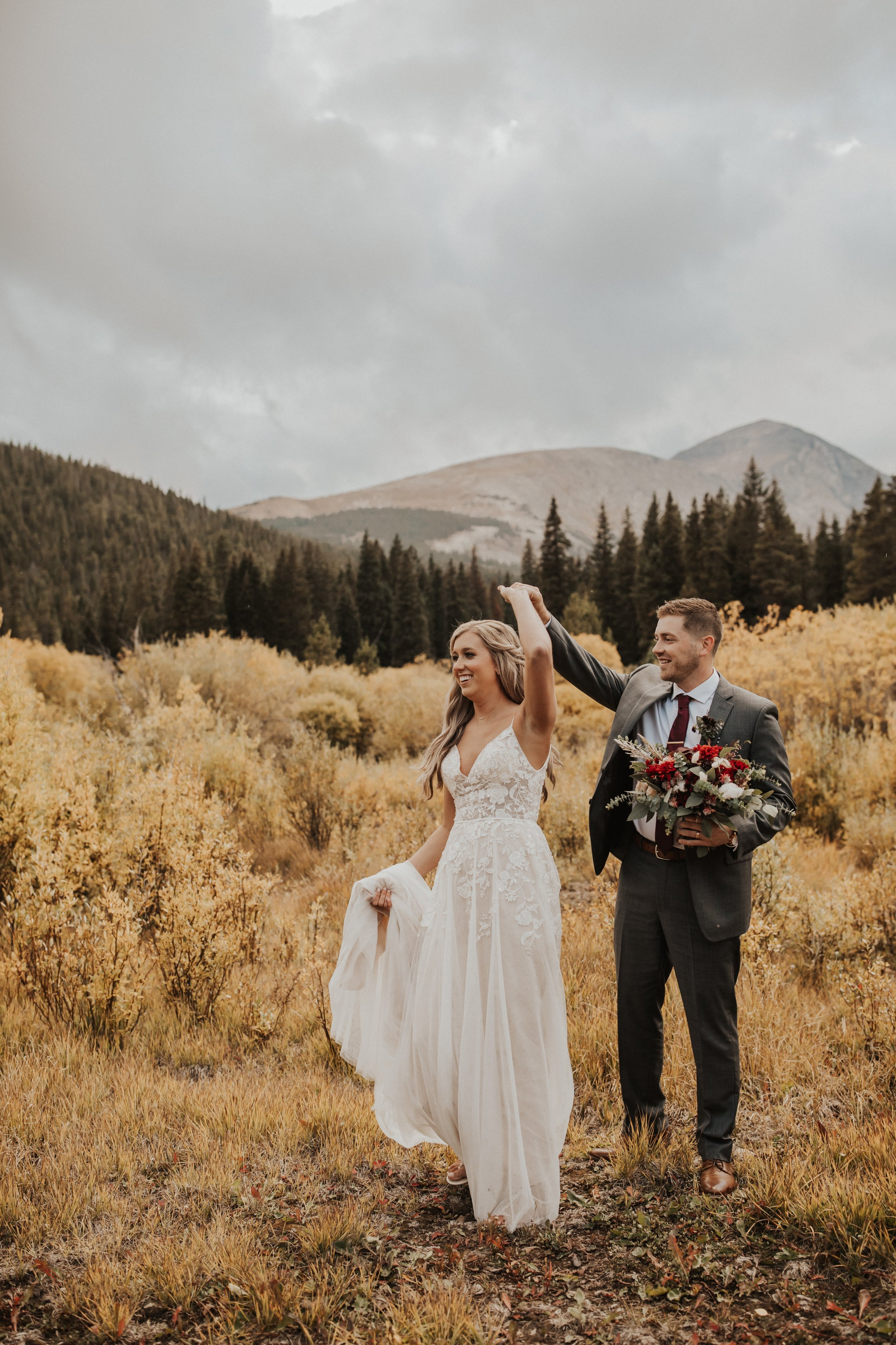 bride and groom dancing with custom floral arrangement at elopement in mountains.jpg