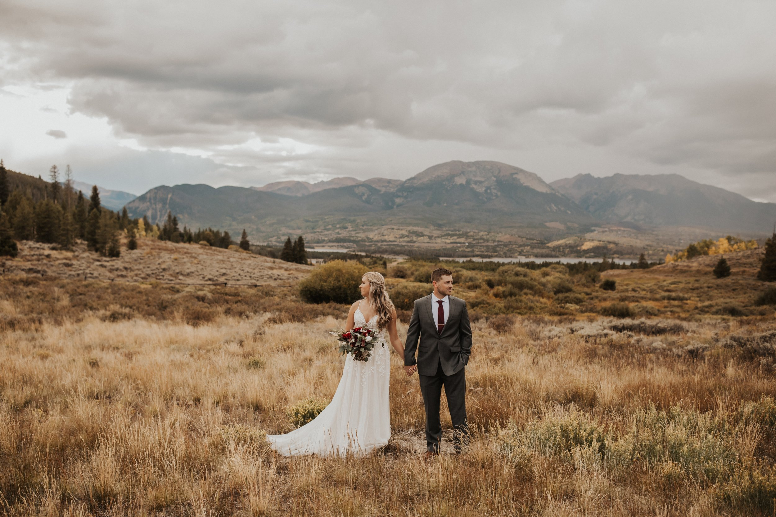 elopement couple standing by mountains with custom bohemian floral arrangement.jpg