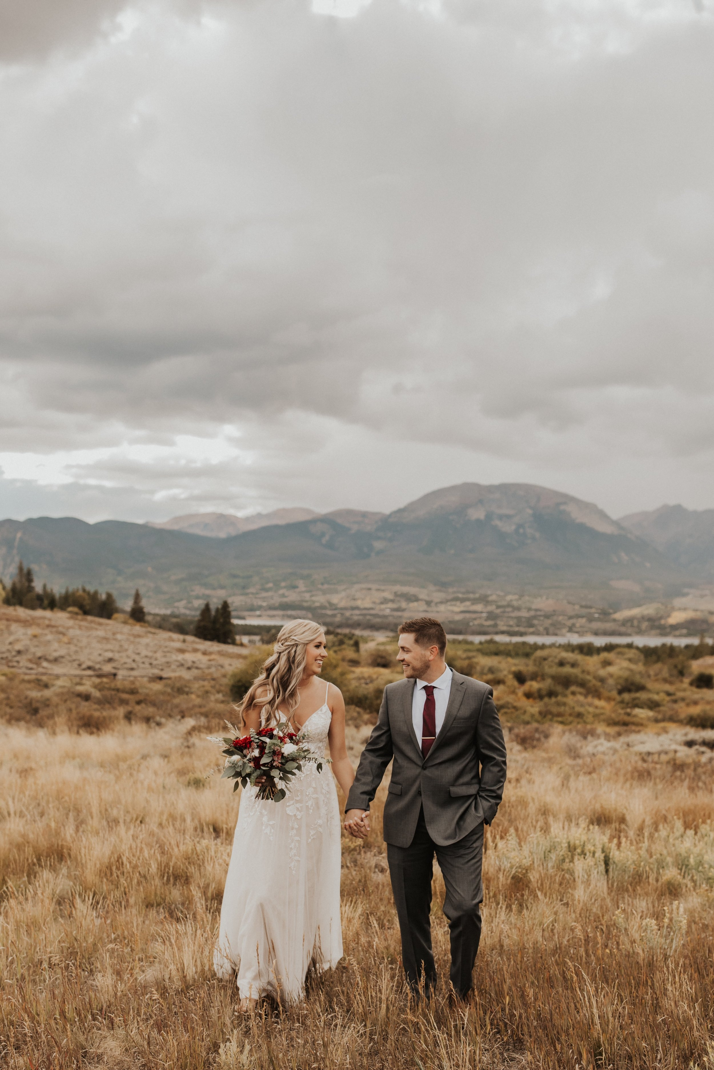 kansas city elopement couple standing by mountains with unique summer bouquet.jpg