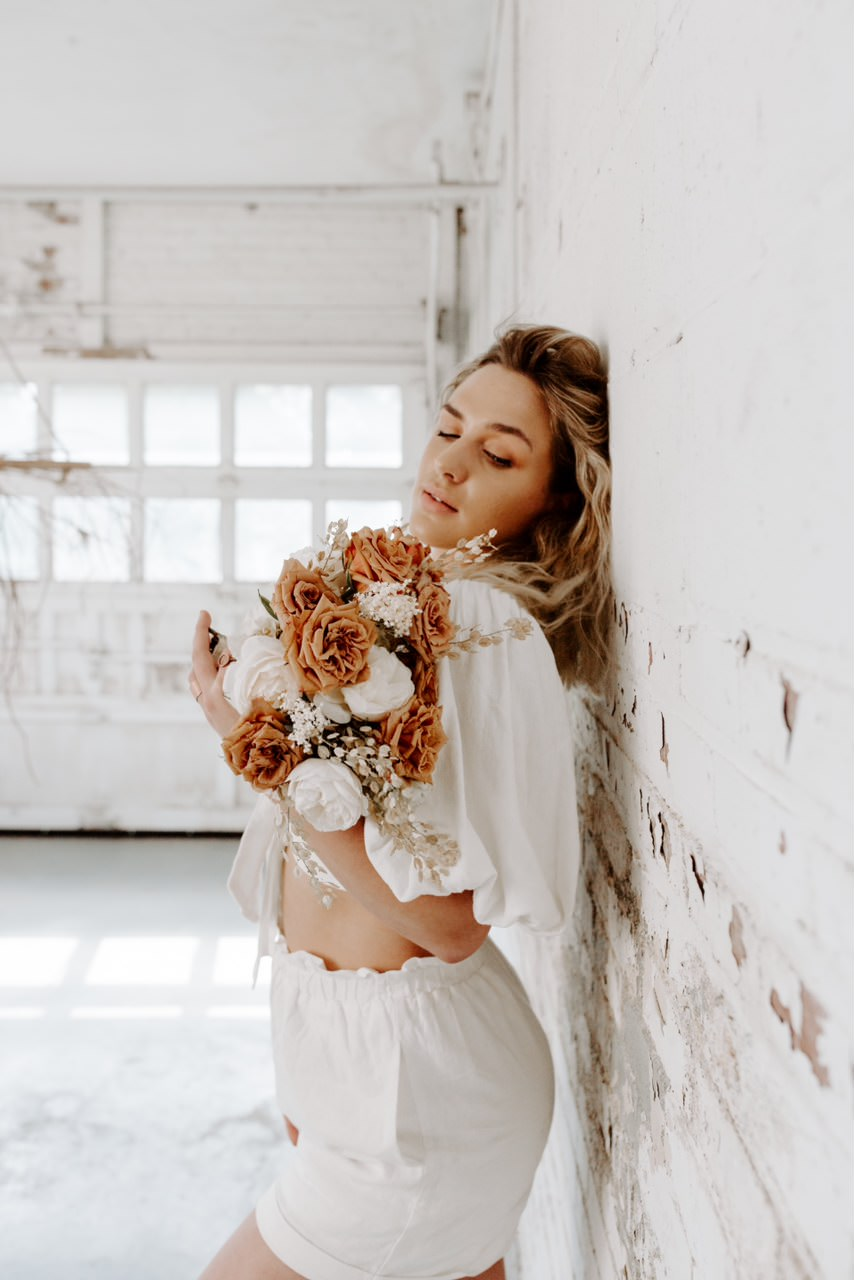 bohemian girl in bright warehouse holding custom floral arrangement.jpg
