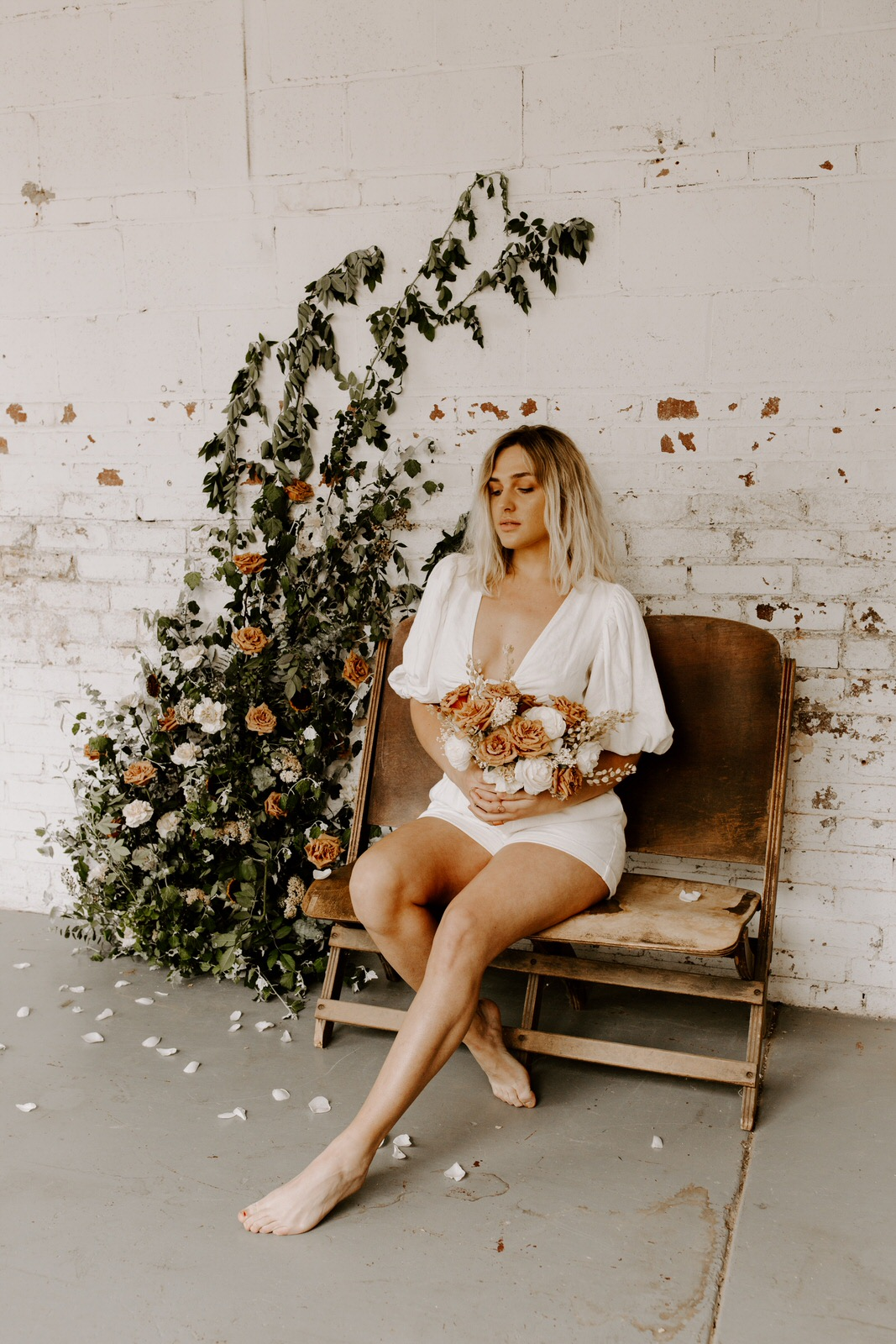 bohemian model sitting in rustic warehouse setting with custom bouquet for photography collaboration.jpg