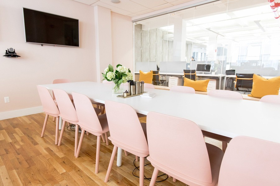 A beautiful conference room, in Small Girls PR's New York office, simple and elegant, featuring a glass wall open to the rest of the office.