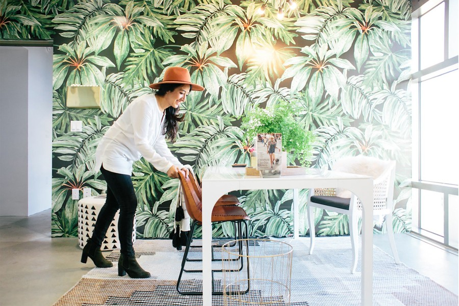 SGPR's LA office boasts a conference room with a glass wall overlooking LA and a wall covered in a large leafy green wallpaper.