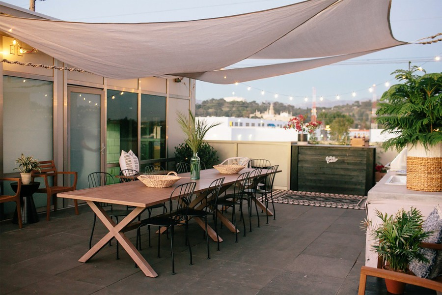 A beautiful rooftop terrace with a large wooden table, green plants, string lights, and sun sails to protect from the elements.