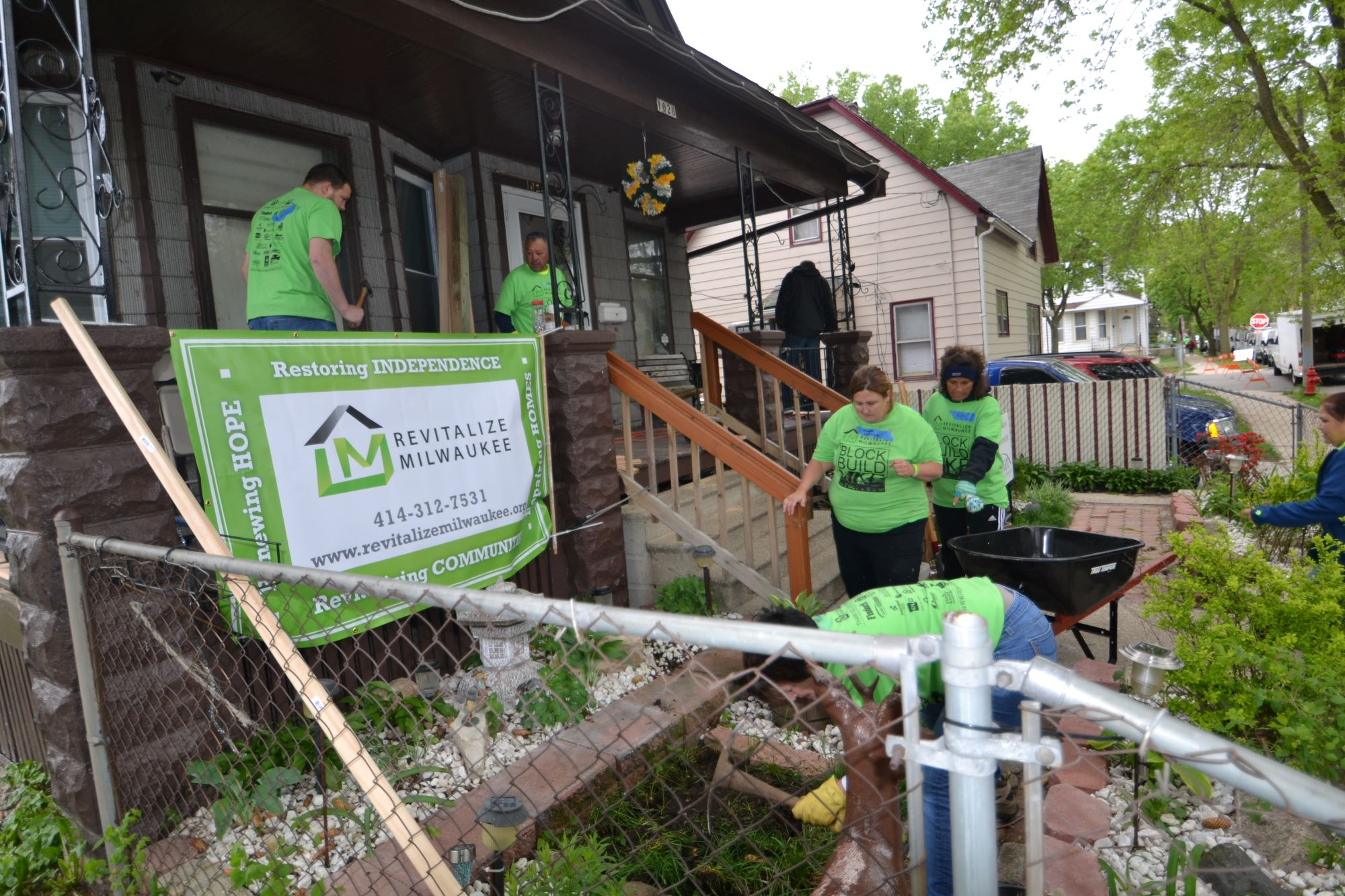 Volunteers repairing a porch and cleaning front yard.